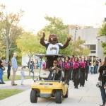 true grit mascot rides vehicle dance team behind him