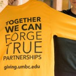 Person holding up a UMBC t shirt