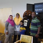 family poses with mascot