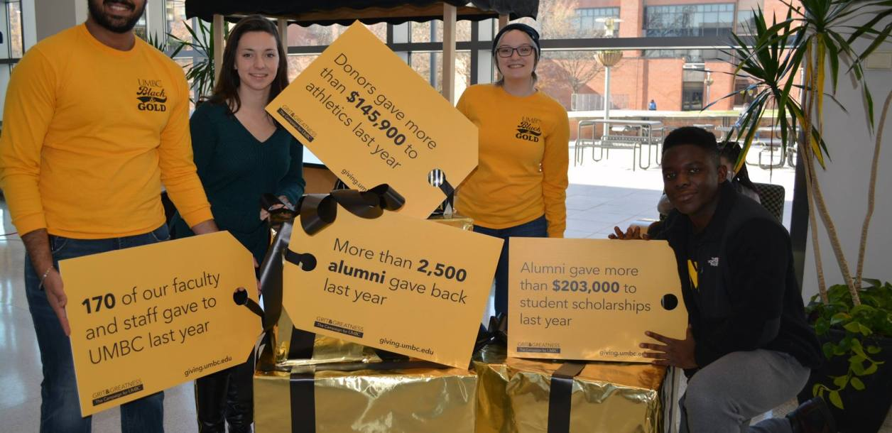 People in black and gold hold donor signs