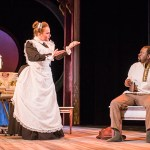 actors in costume perform, maid talks to man drinking on bench