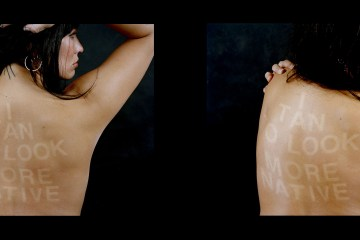 woman posing with I tan to look more native on her back