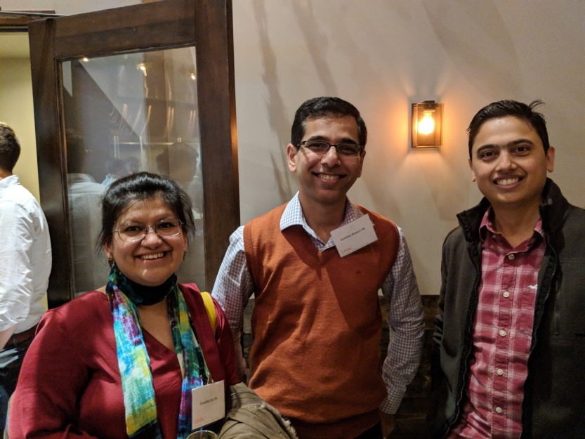 Three people smile posing together at bay area alumni event