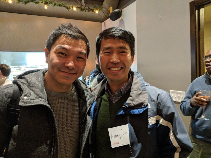 Two guys smile posing together at Bay area alumni event