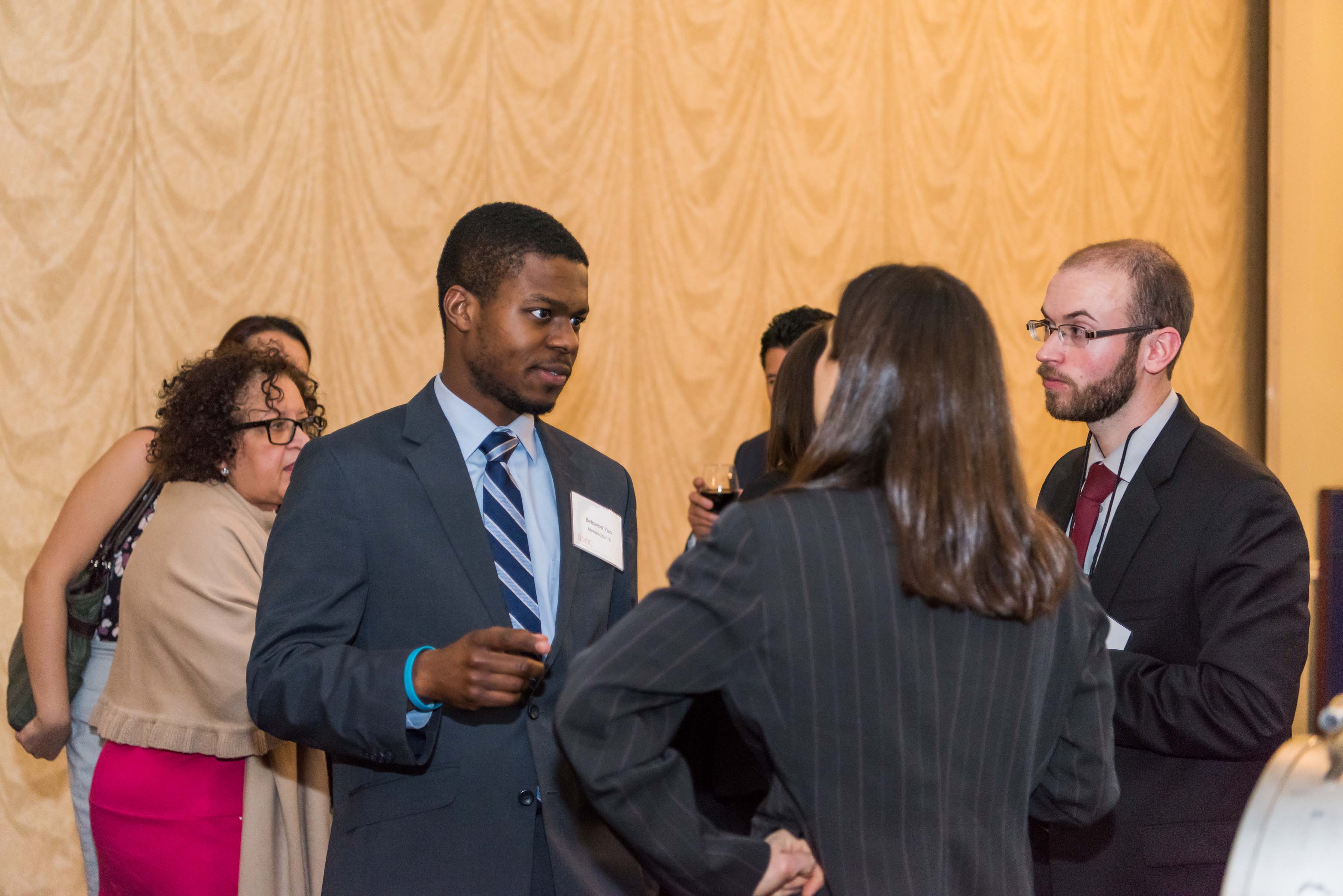 Three people group together and talk at Annapolis Alumni reception