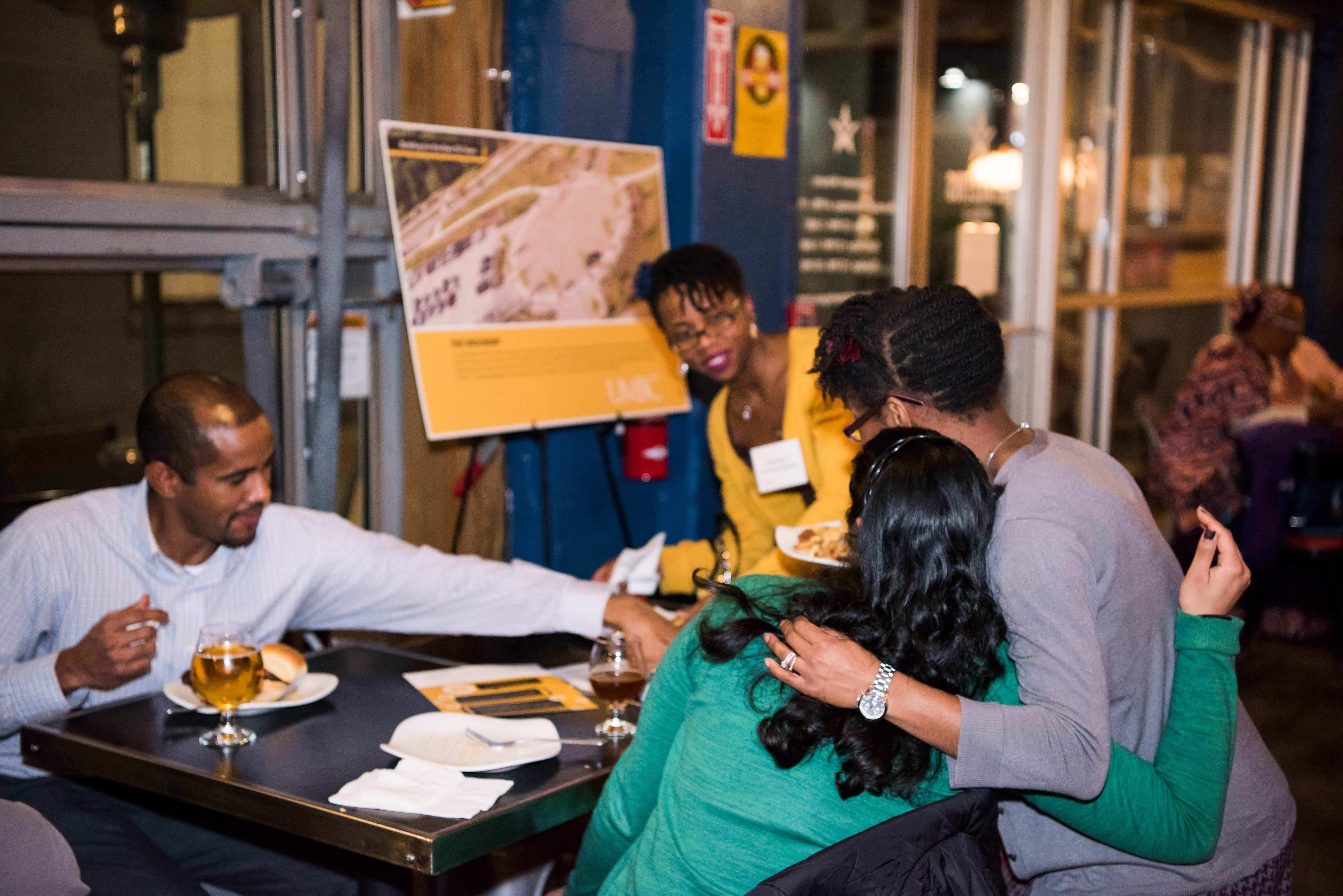 Women embracing as they talk to people at table at chocolate city bar talk