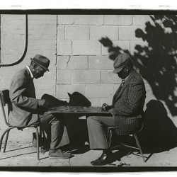Black and white photo of men playing checkers outside