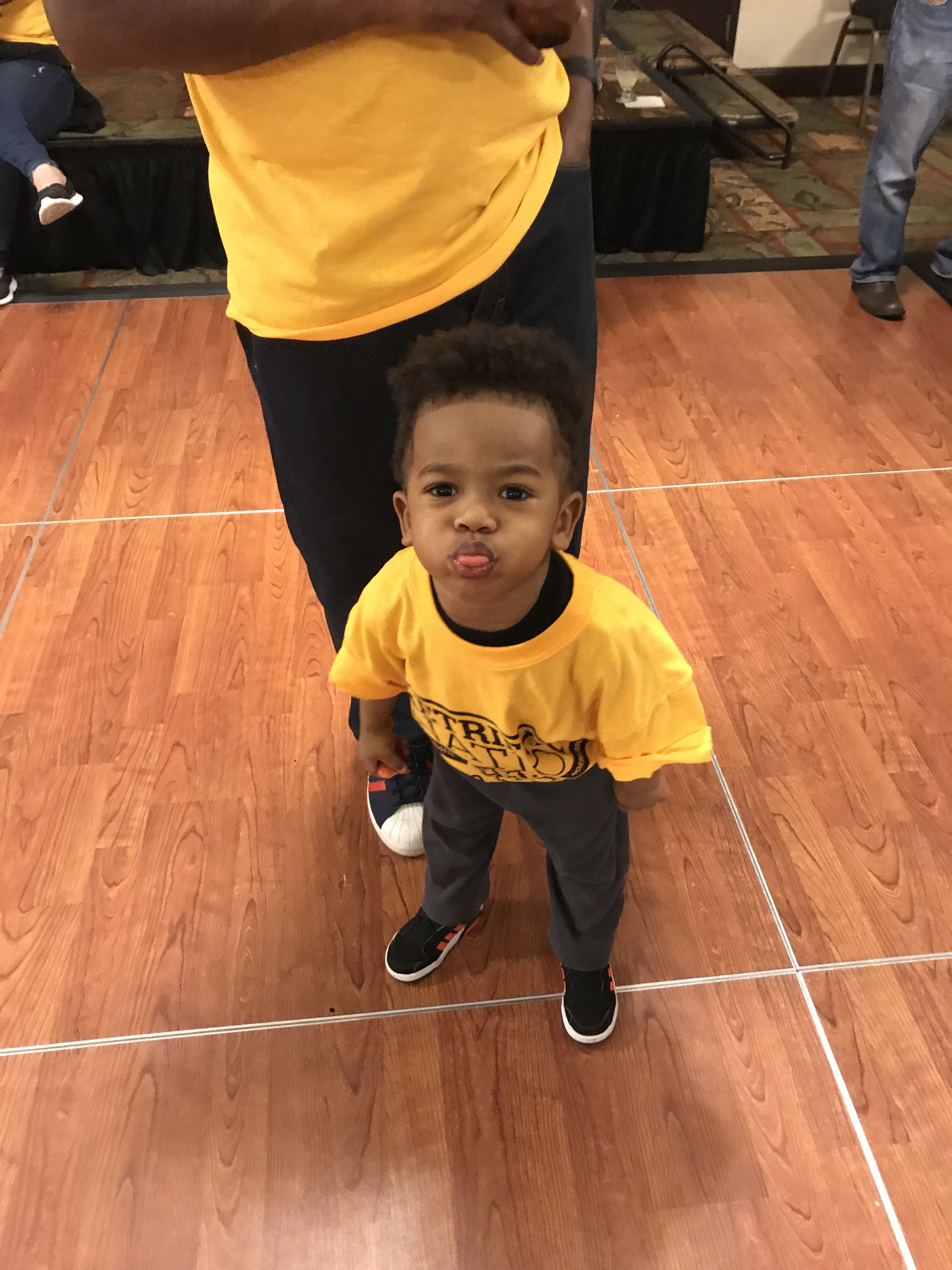 Small child sticks out tongue in UMBC shirt