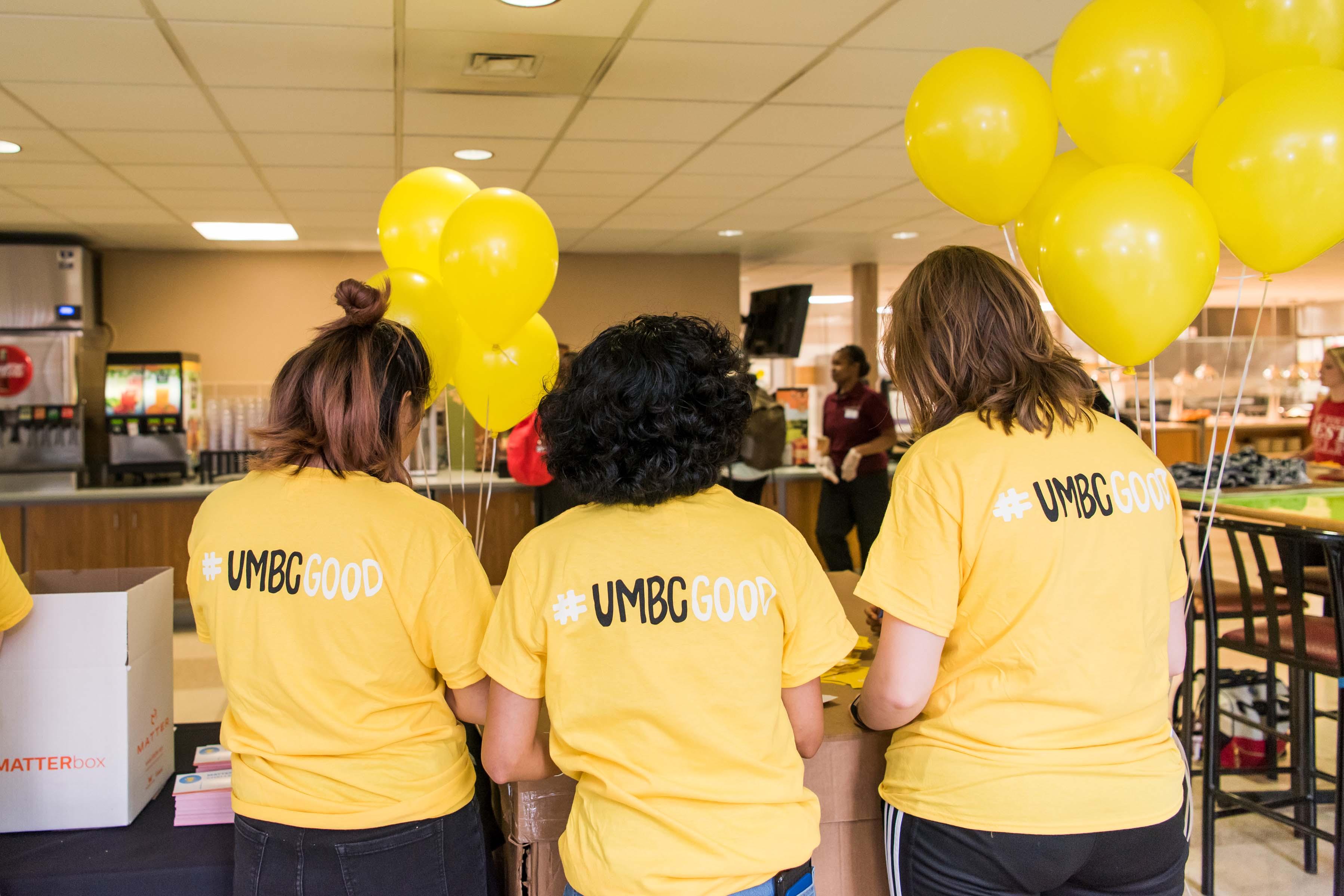 Three people with #UMBCGOOD shirts
