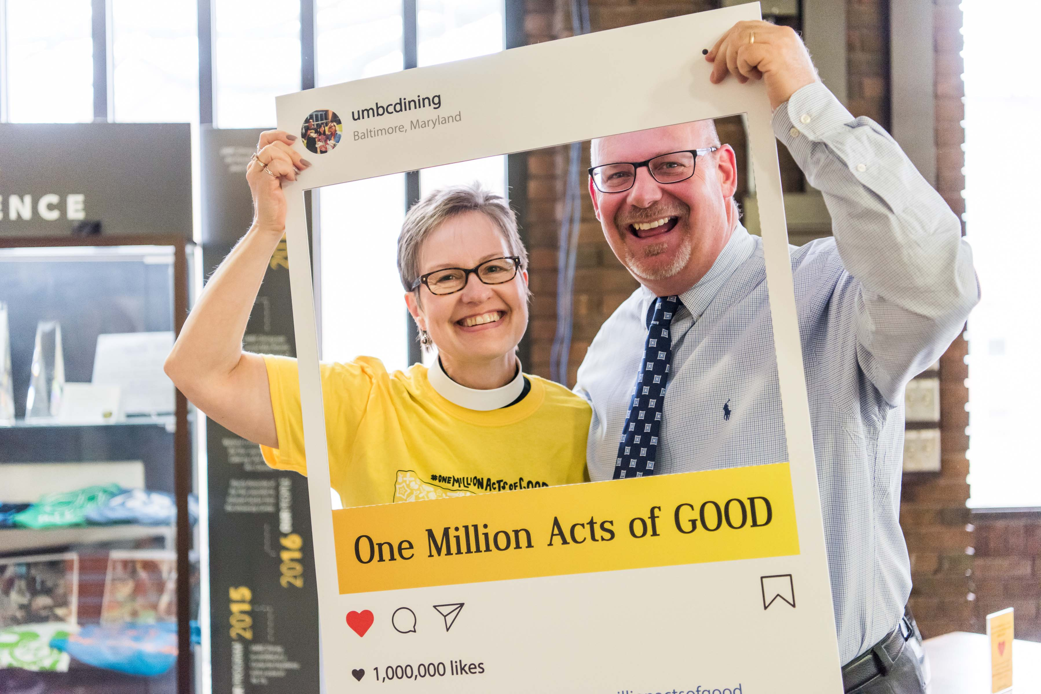 Two people pose with one million acts of good frame