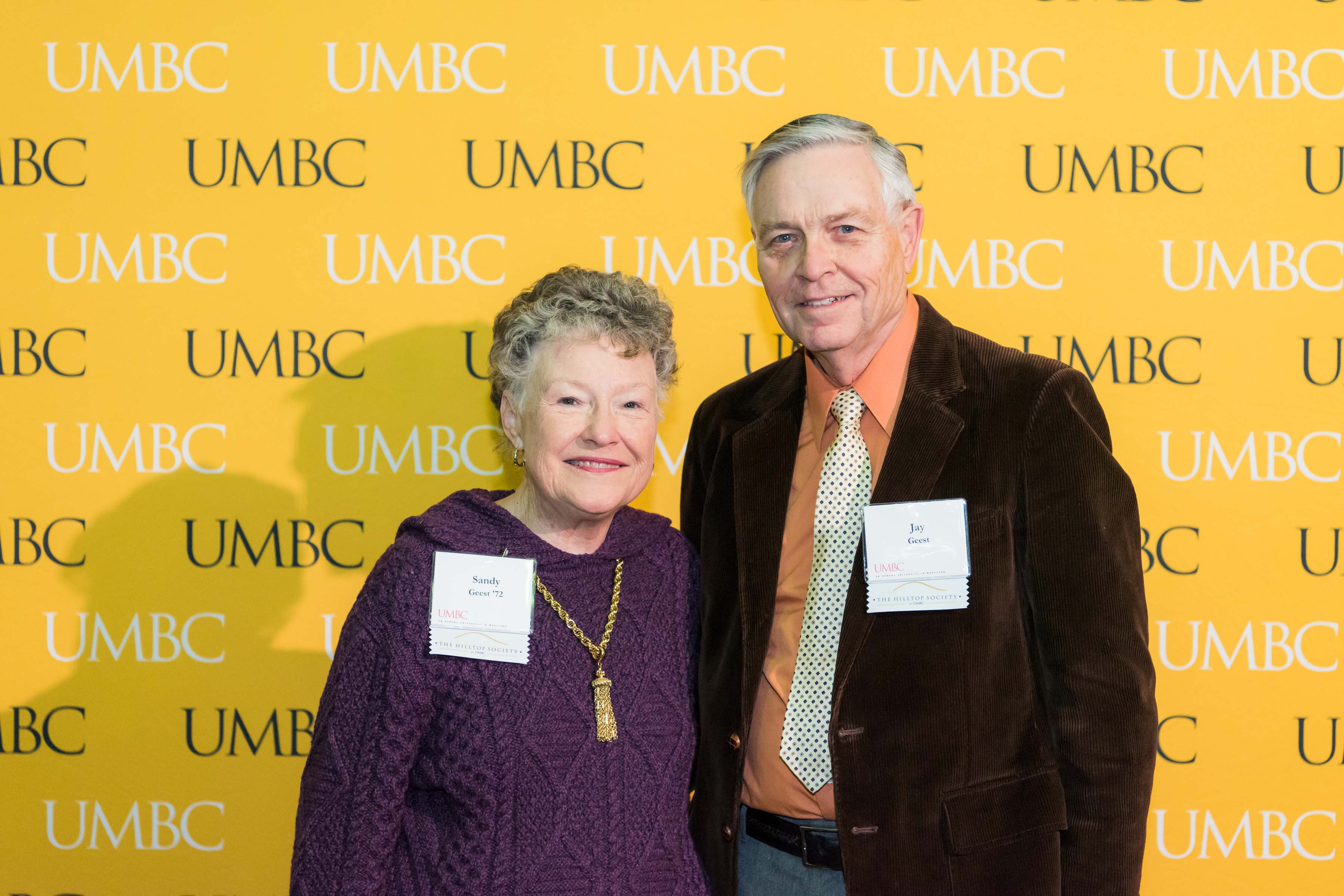 Jay and woman stand in front of UMBC wall for Scholarship luncheon