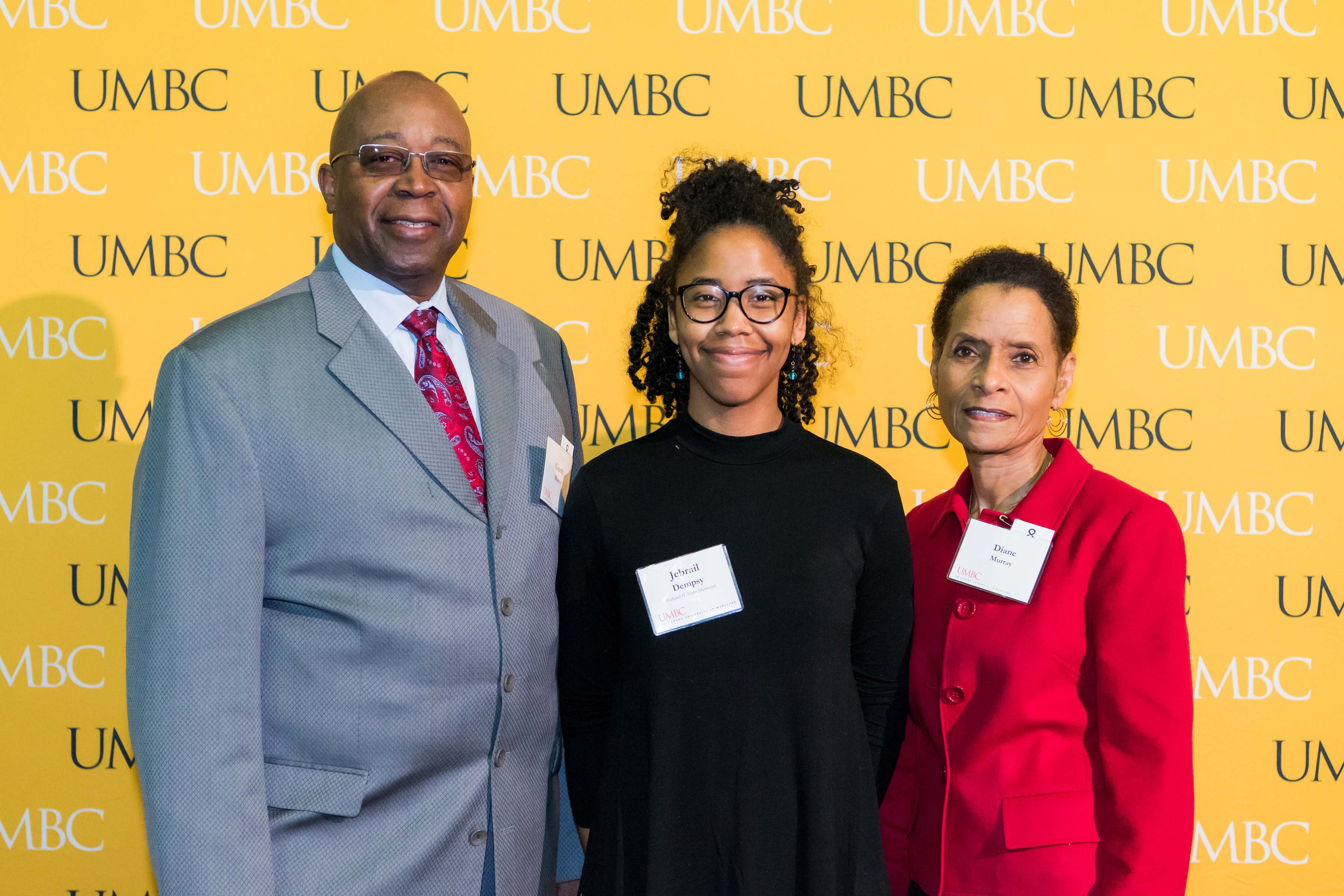 Three people pose in front of the UMBC wall at the scholarship luncheon