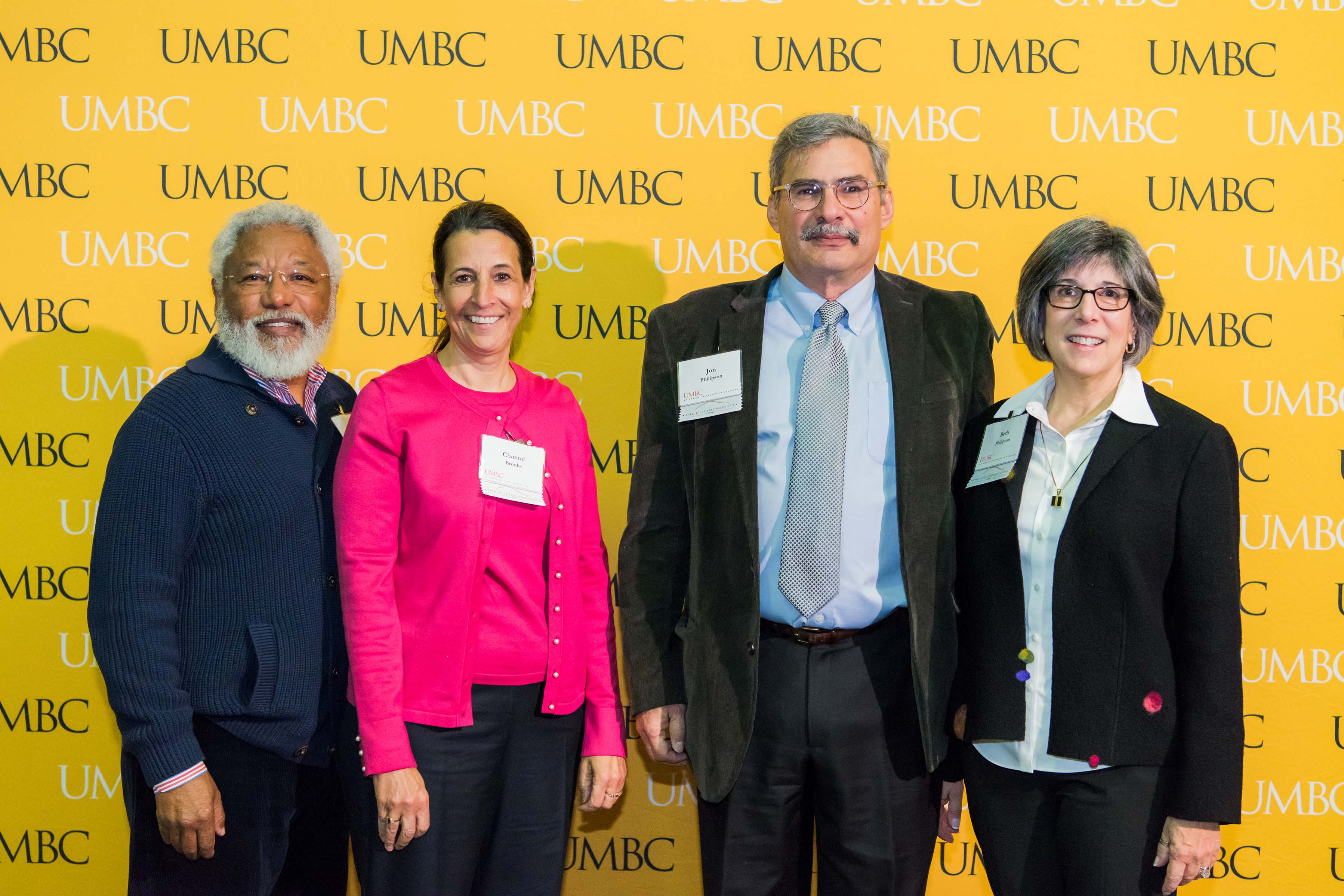 Two couples pose in front of the UMBC wall at the scholarship luncheon