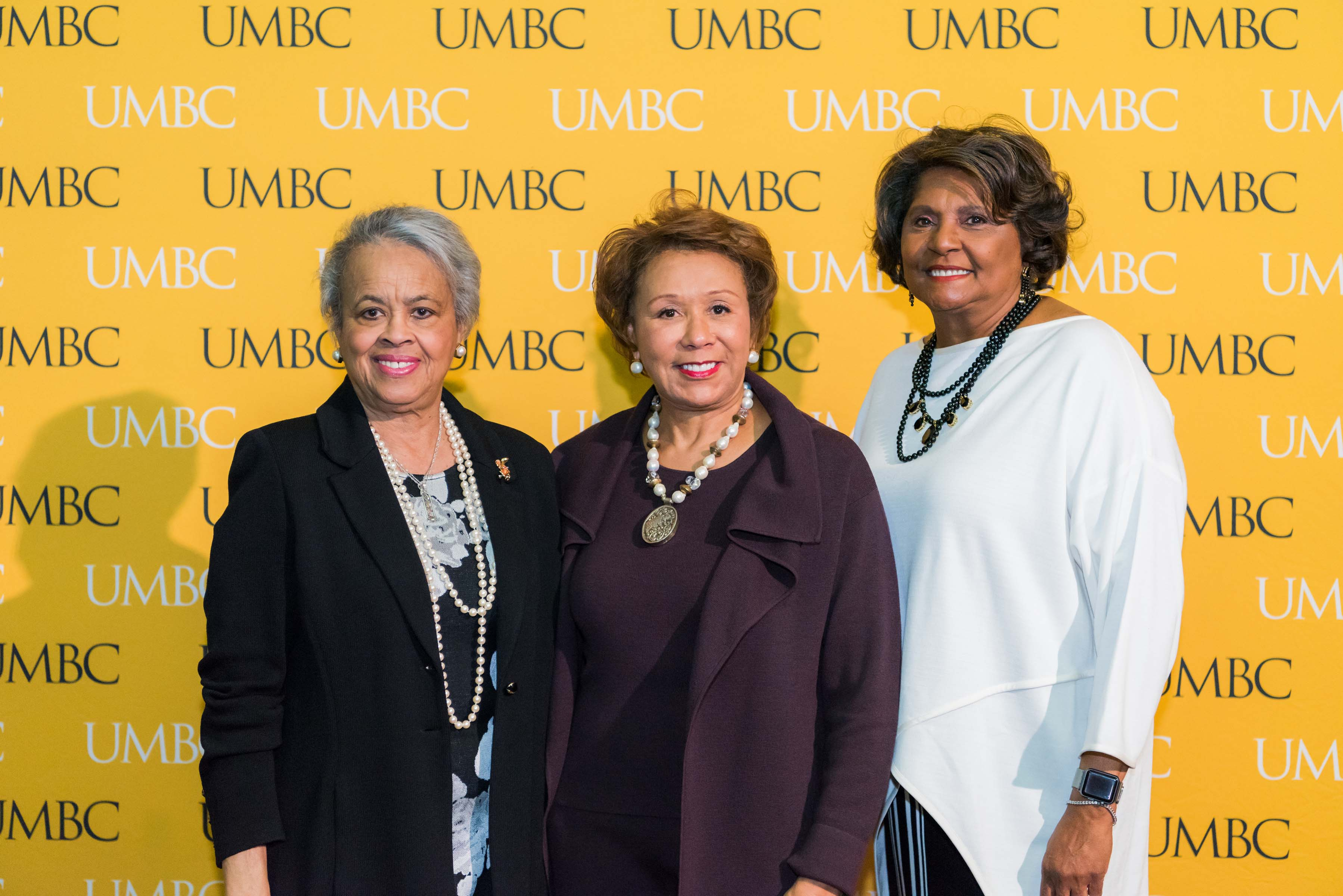 Two people and Jacqueline Hrabowski pose in front of the UMBC wall at the scholarship luncheon