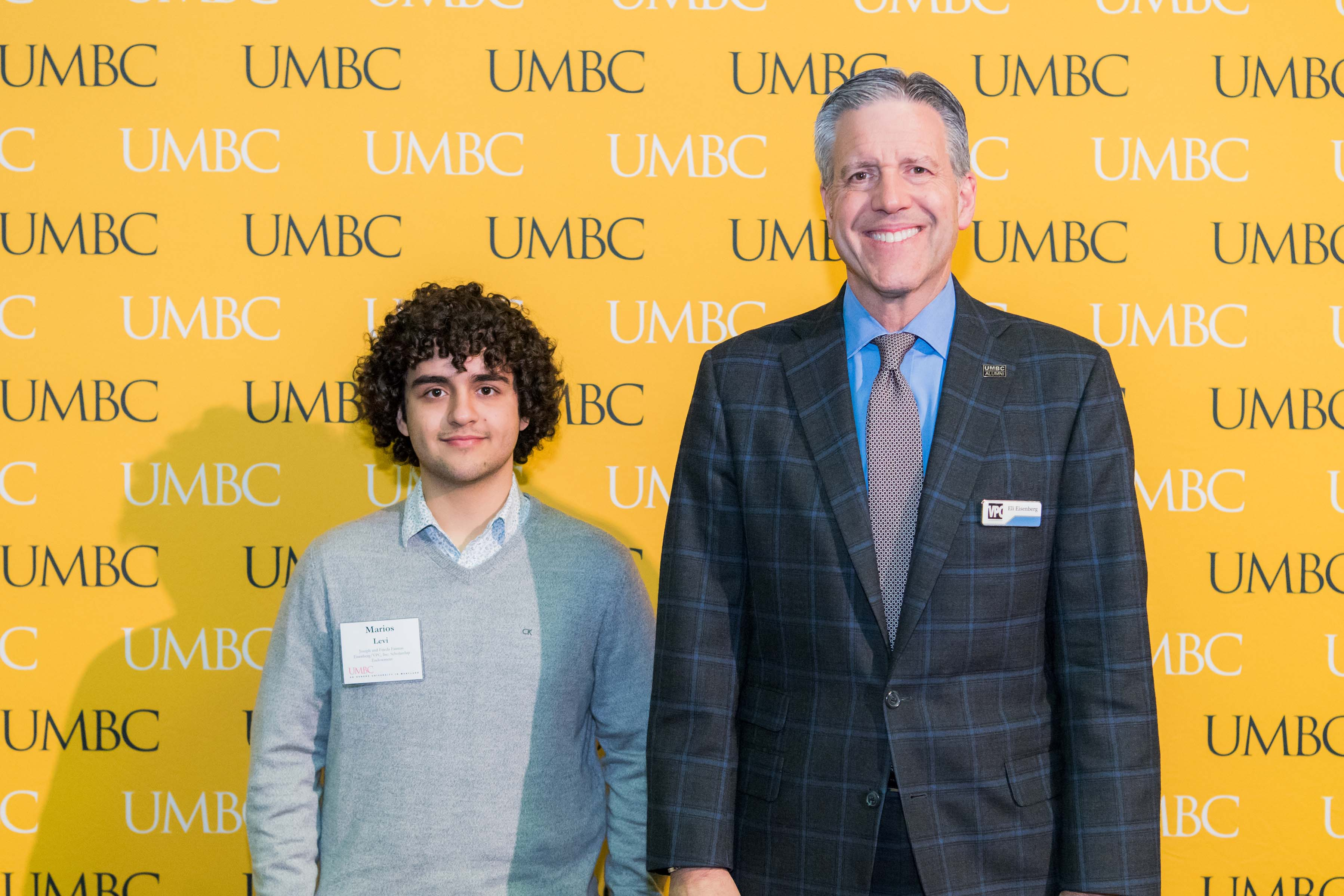 Two men pose in front of the UMBC wall at the scholarship luncheon