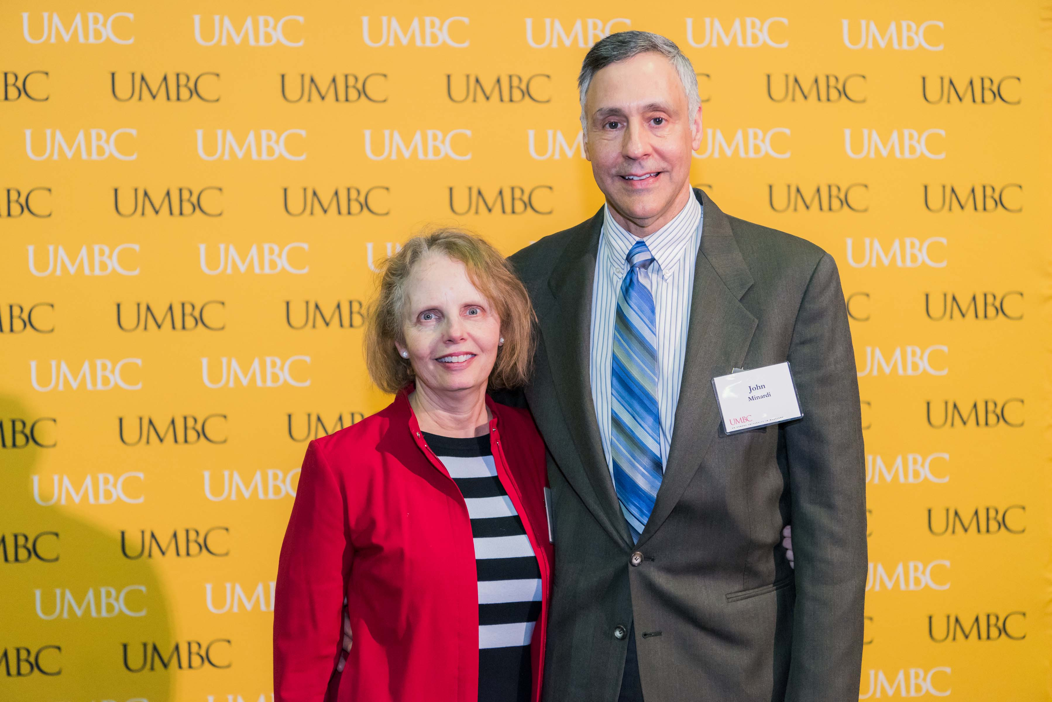 Couple pose in front of the UMBC wall at the scholarship luncheon