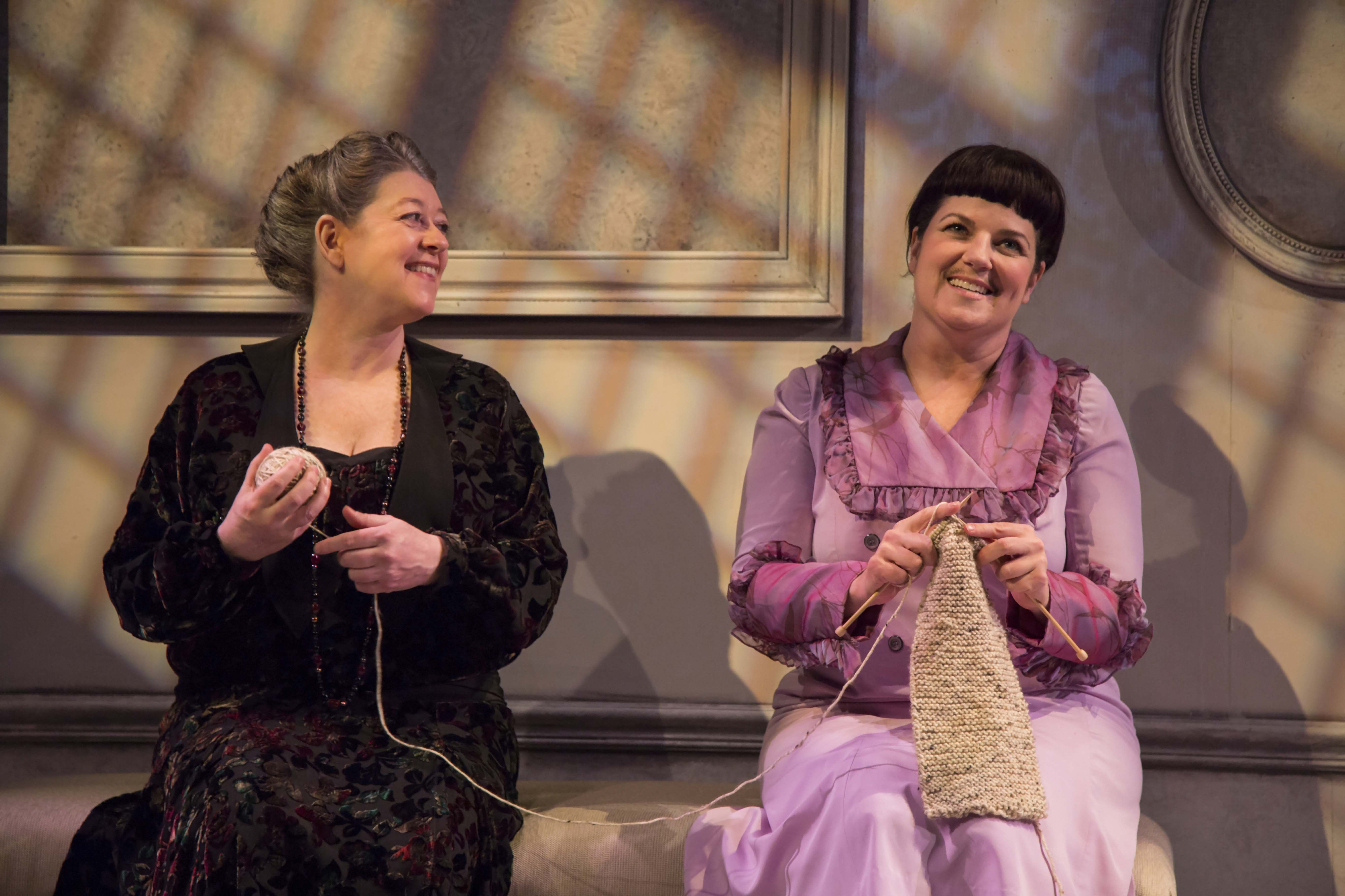 Two women knit on stage