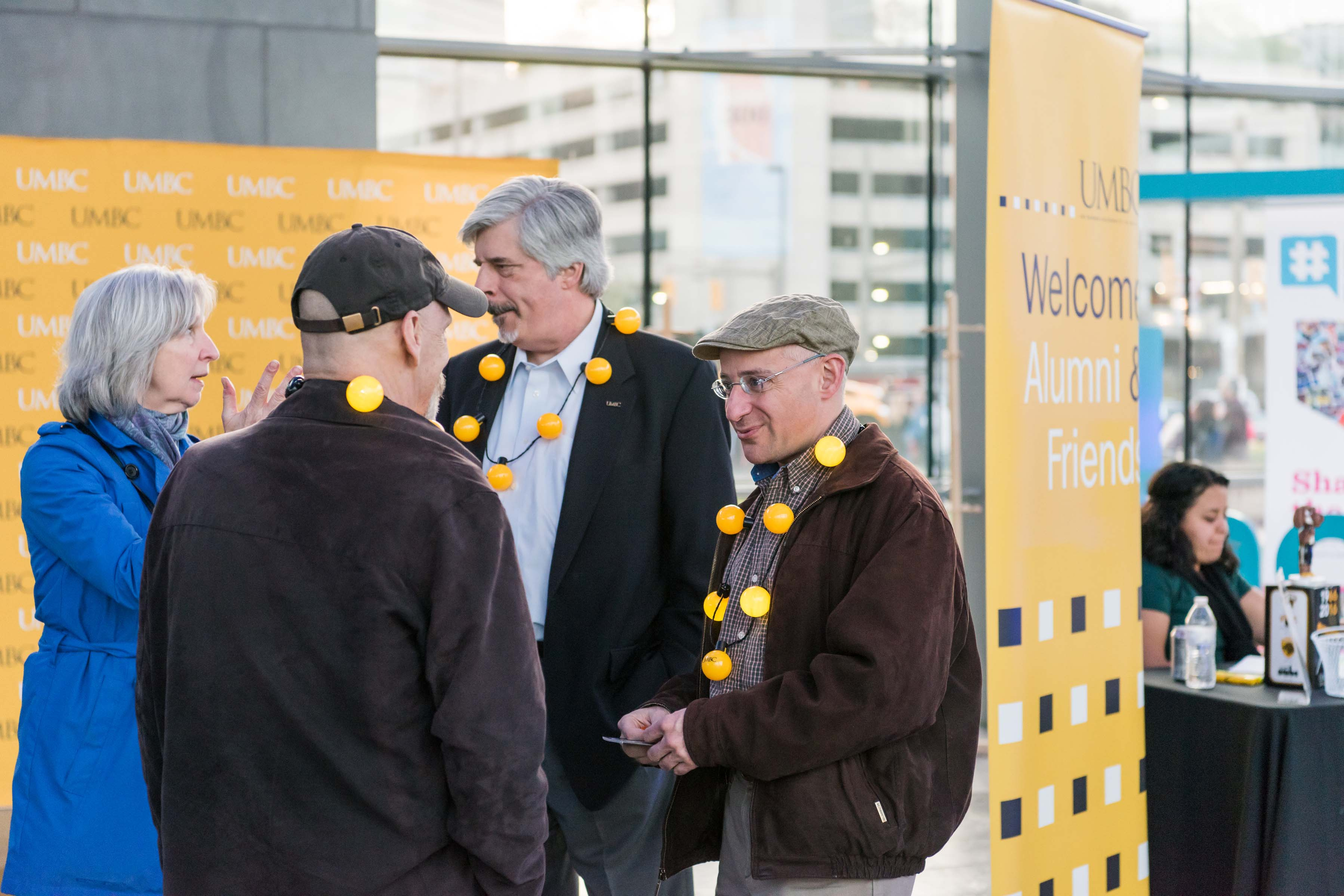 Staff interacting with welcome alumni sign behind them