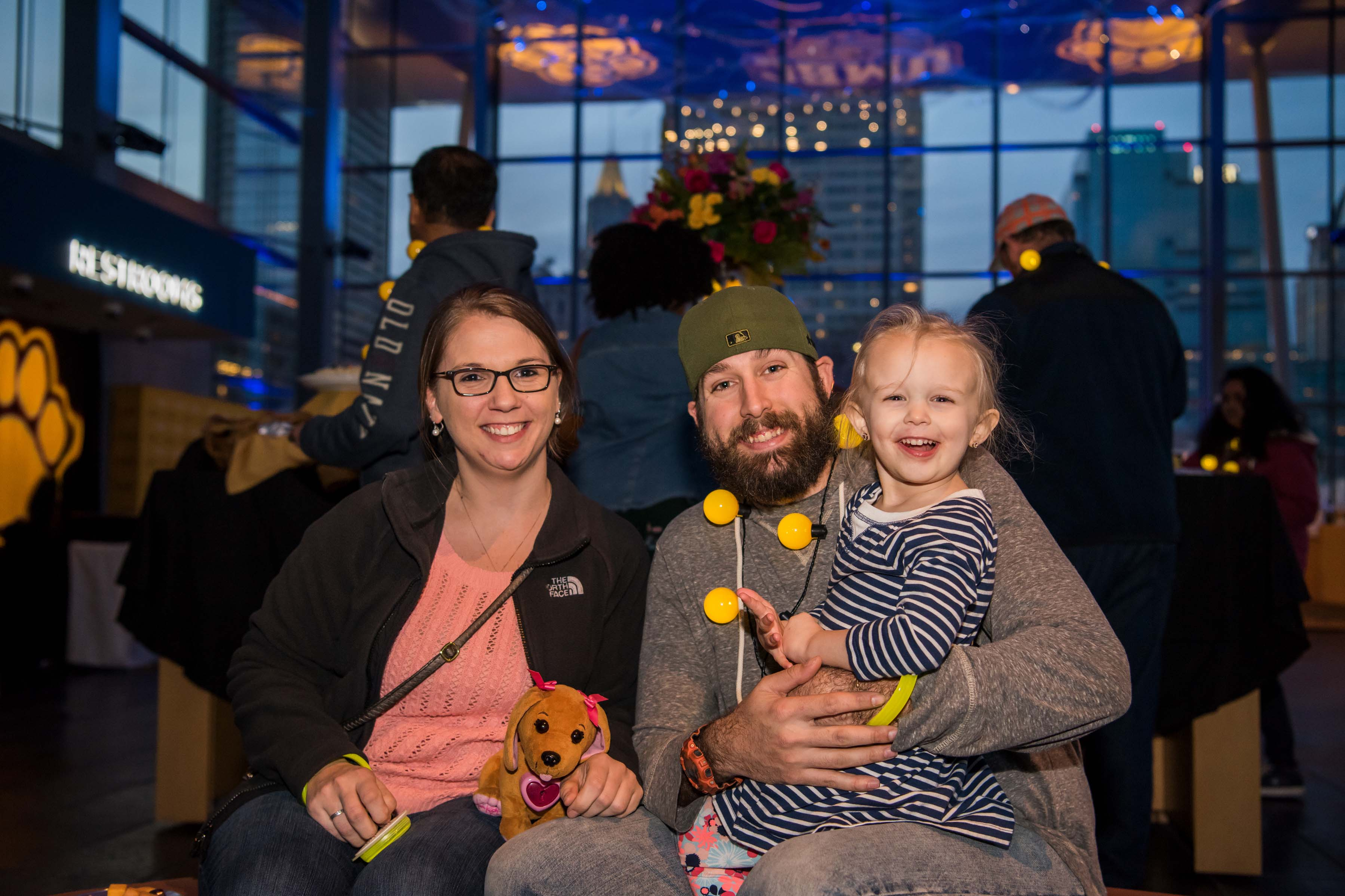 Family sit and pose at light city alumni reception