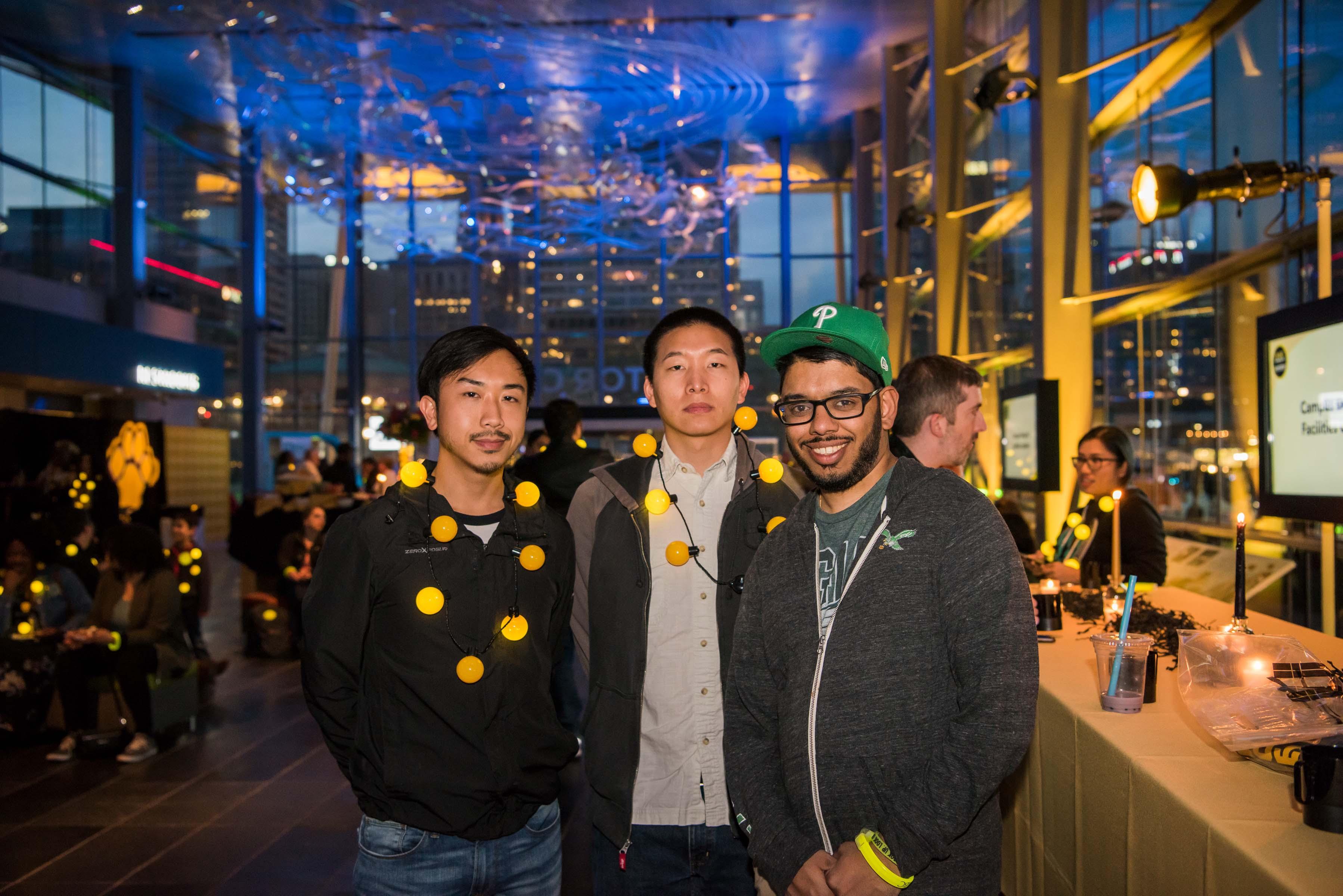 Three guys pose together at light city alumni reception