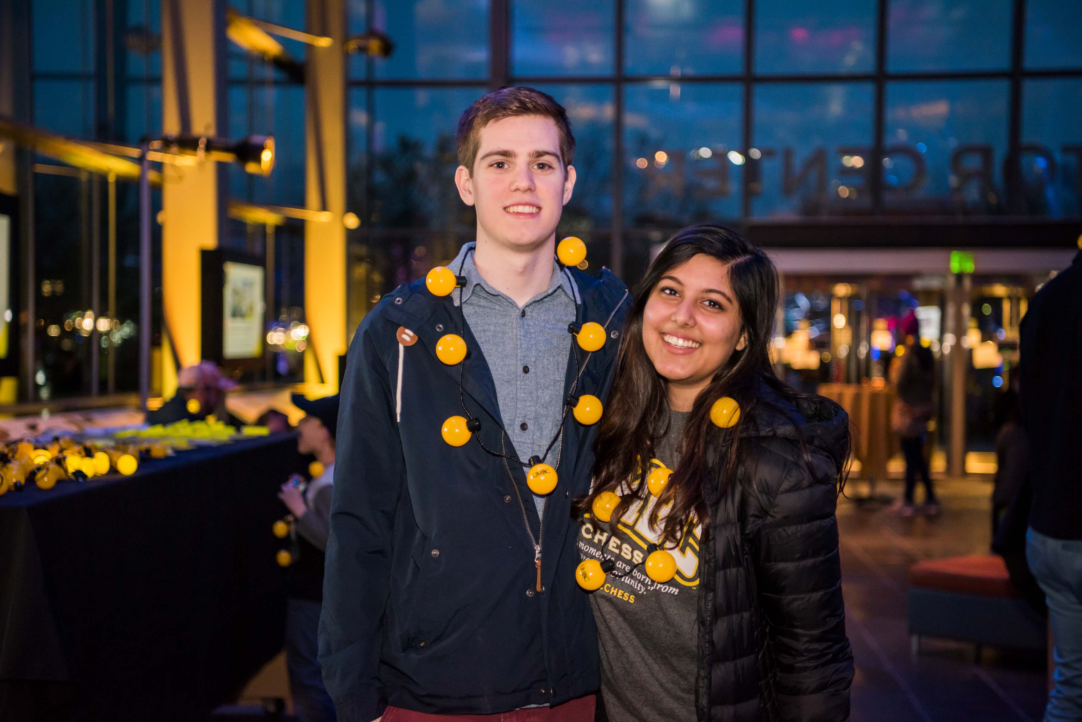 Two people pose together in lobby at Alumni reception
