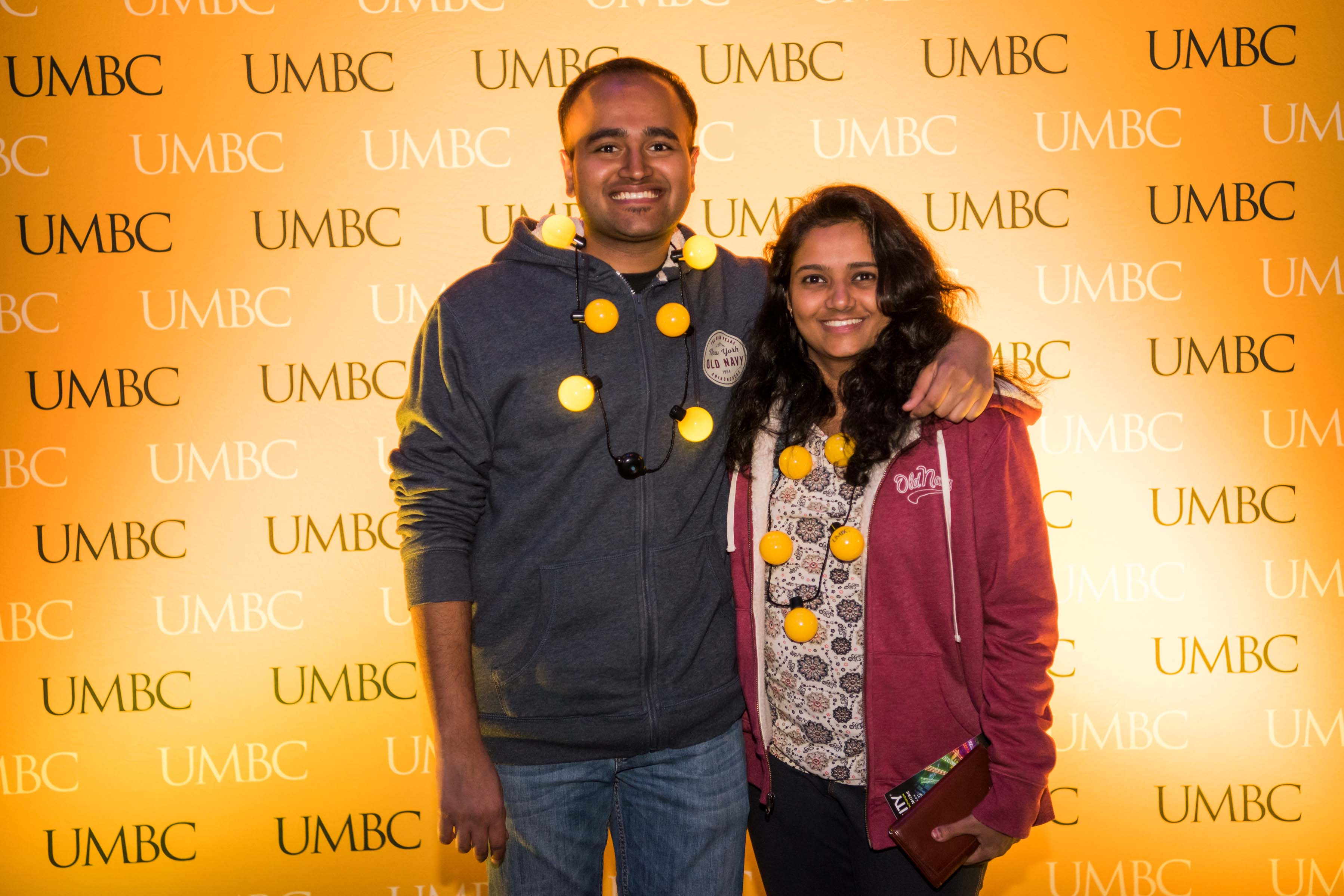 Couple pose in front of UMBC wall at alumni reception