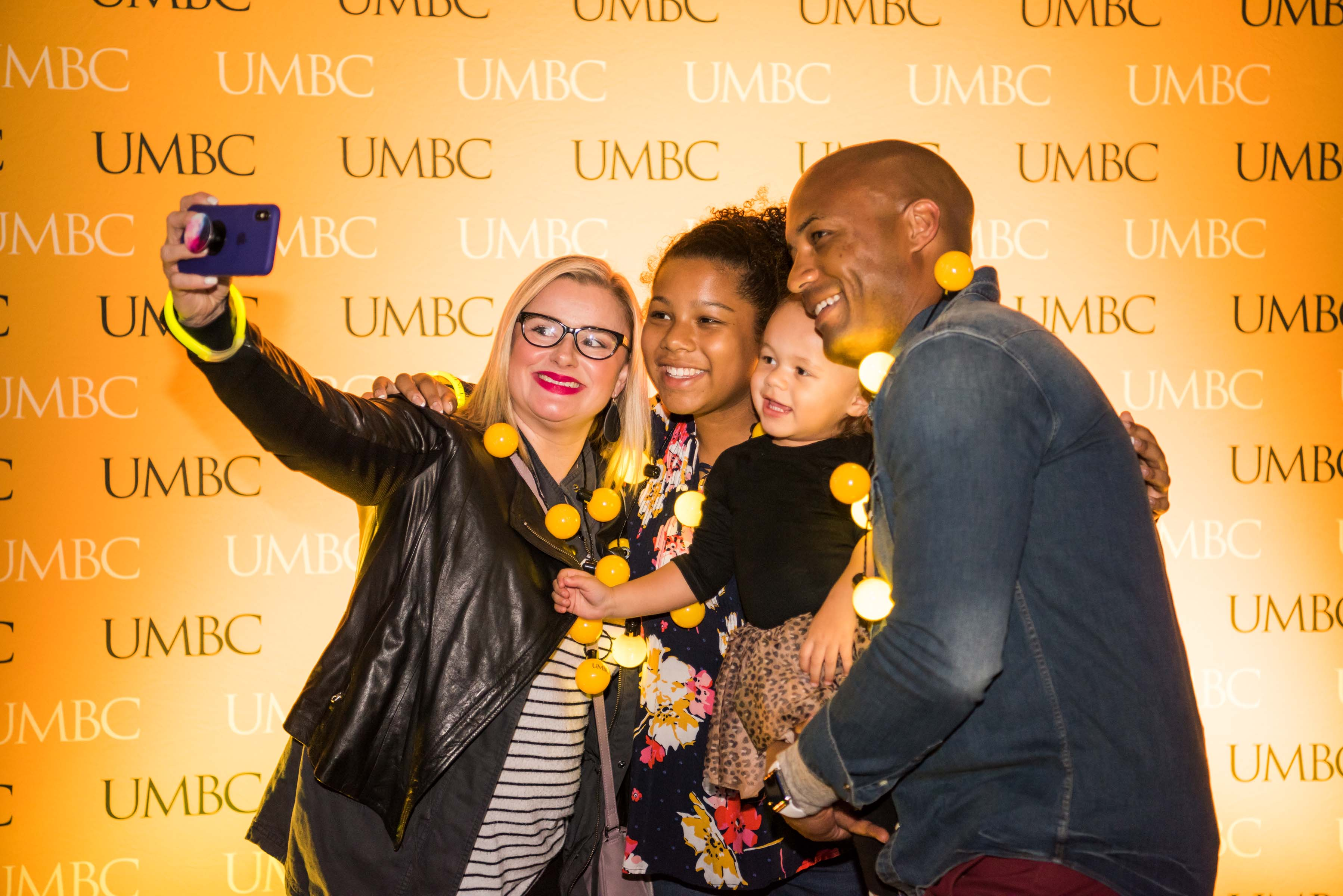 Family takes selfie in front of UMBC wall at alumni reception