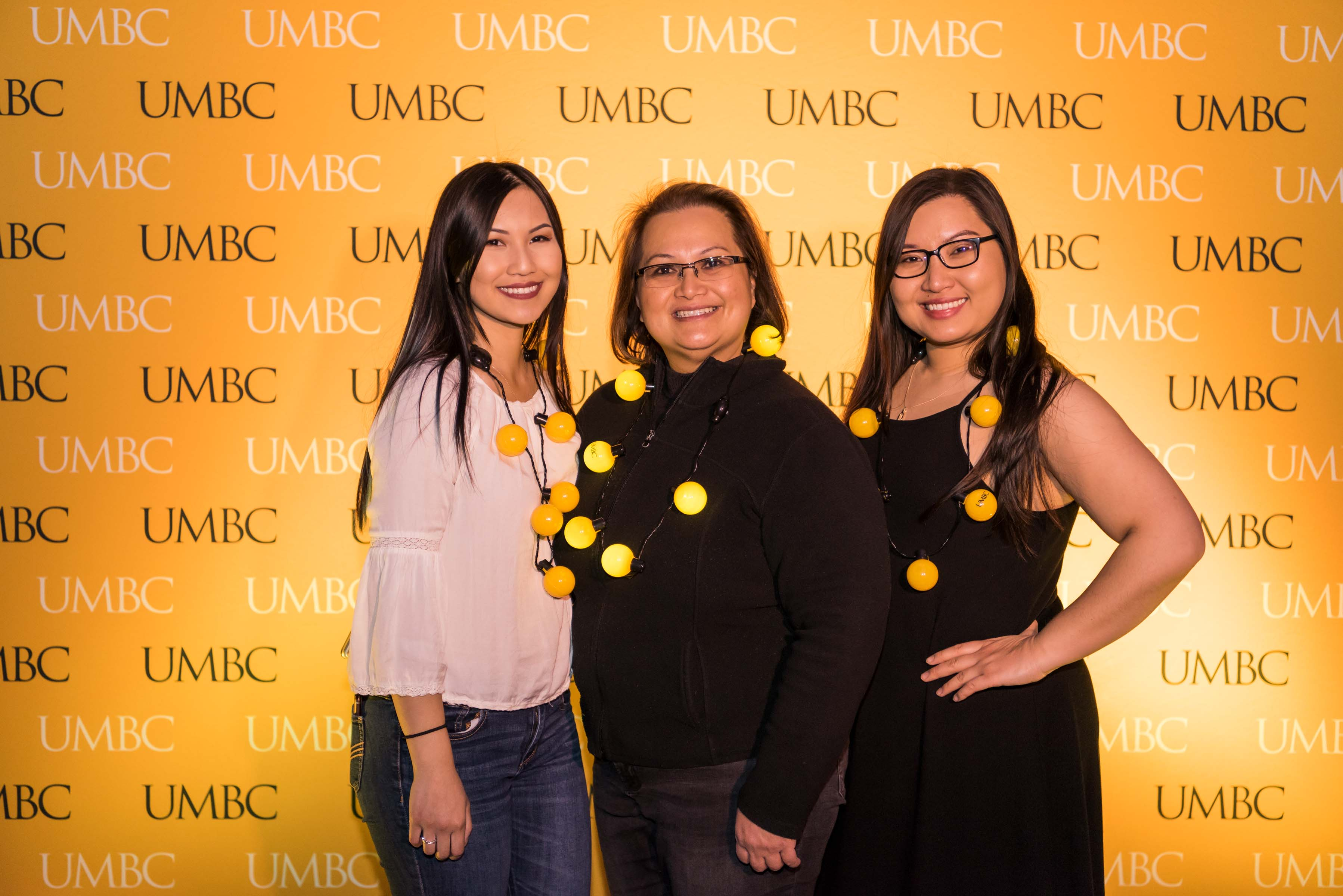 Three women pose in front of UMBC wall at alumni reception