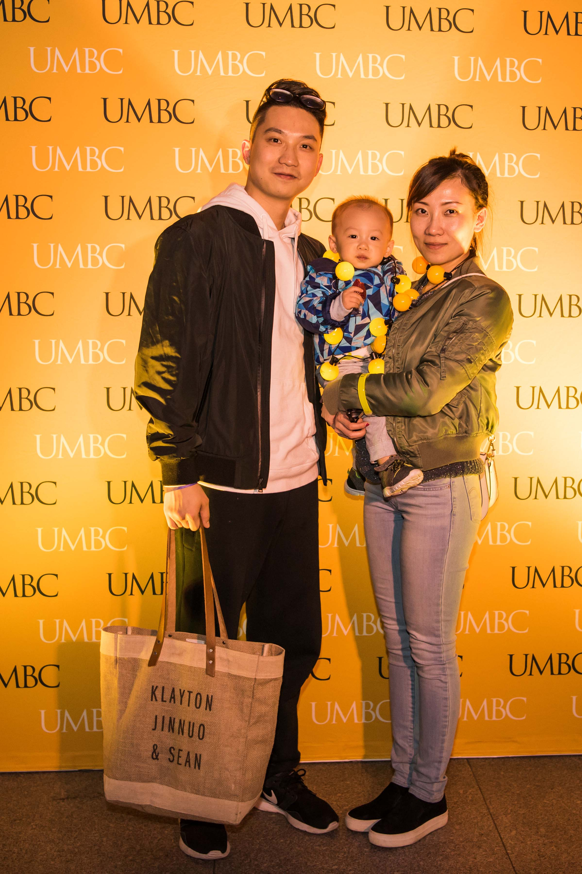 Family pose in front of UMBC wall at alumni reception