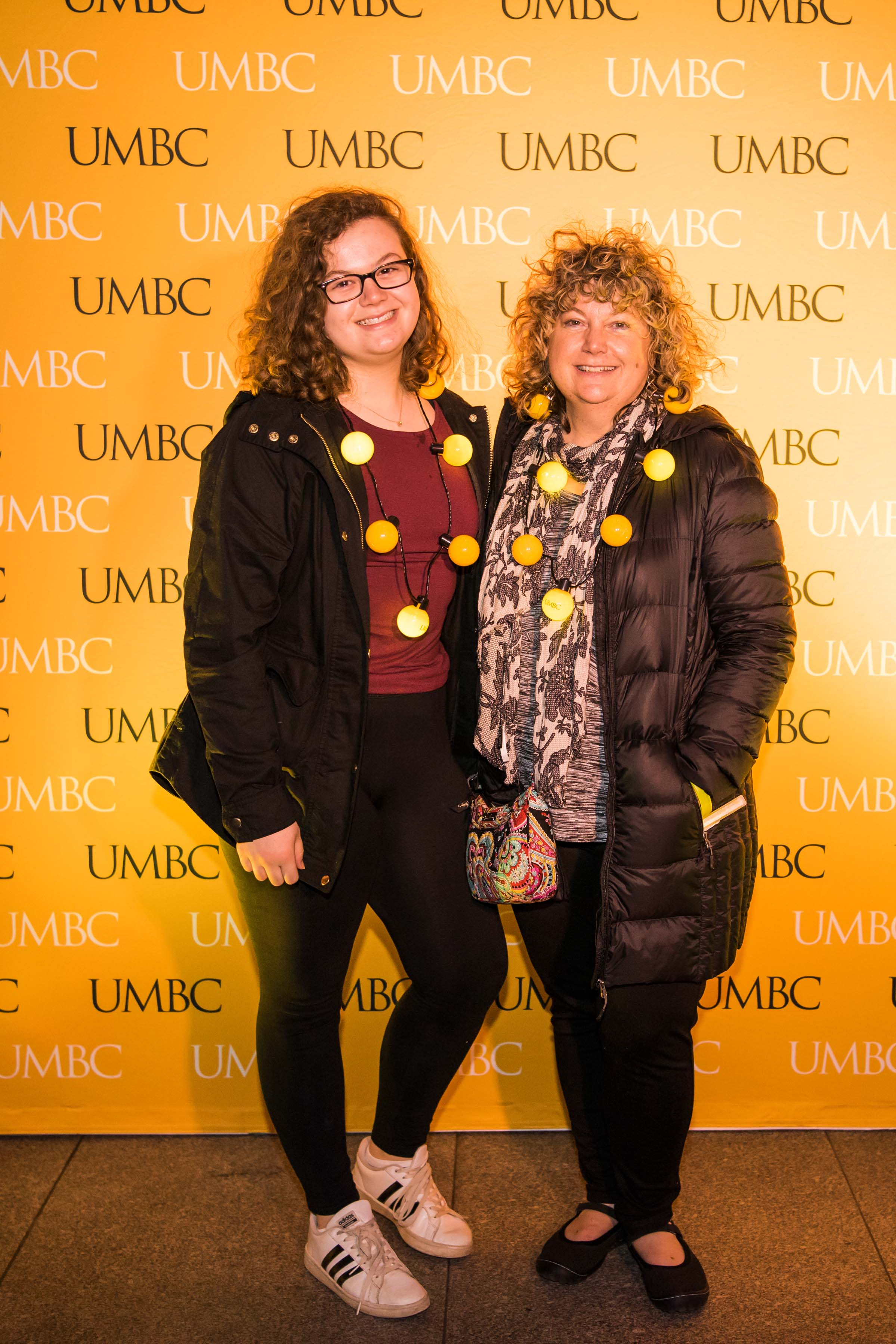Two women pose in front of UMBC wall at alumni reception