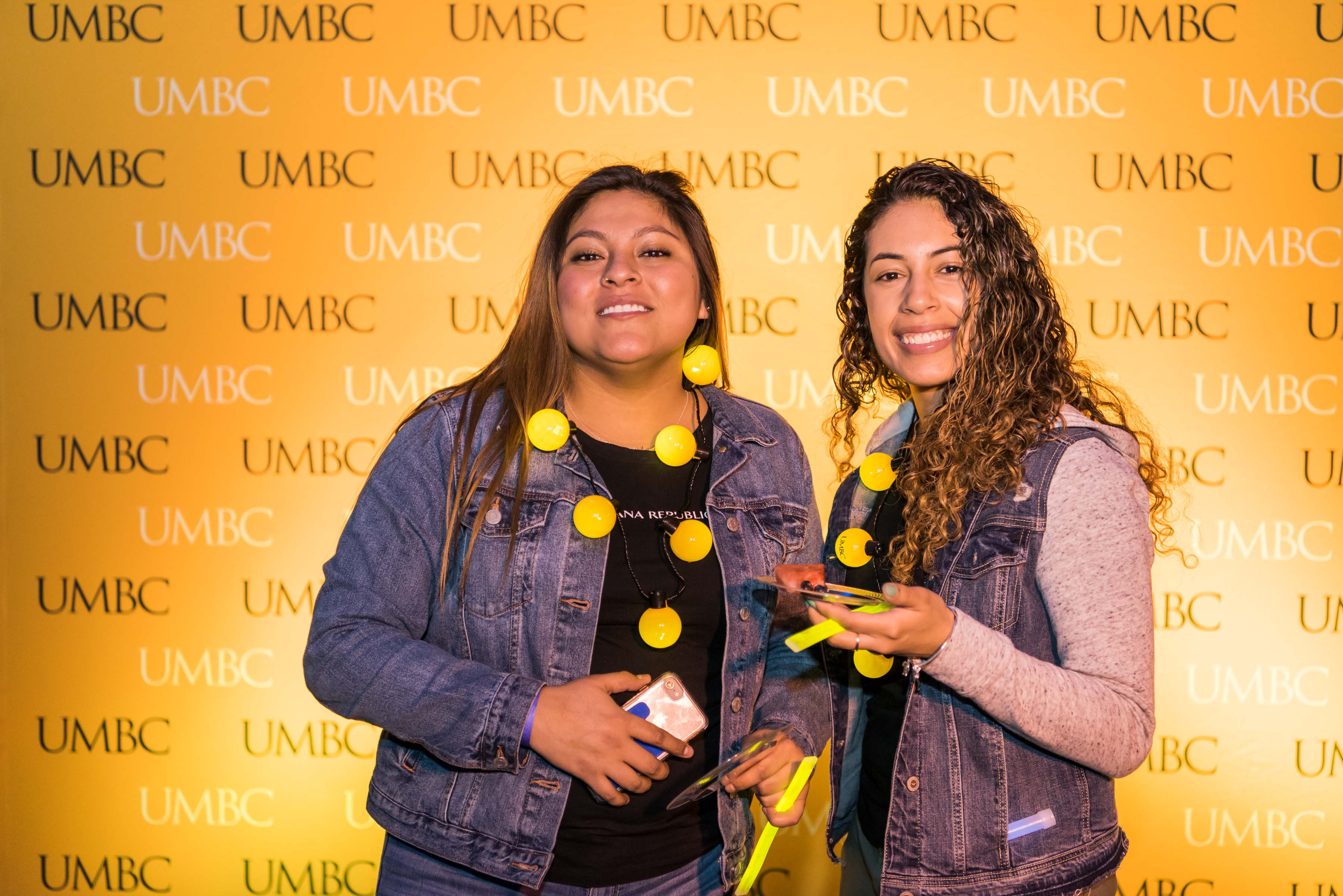 Two women pose in front of UMBC wall at Pier 5 reception