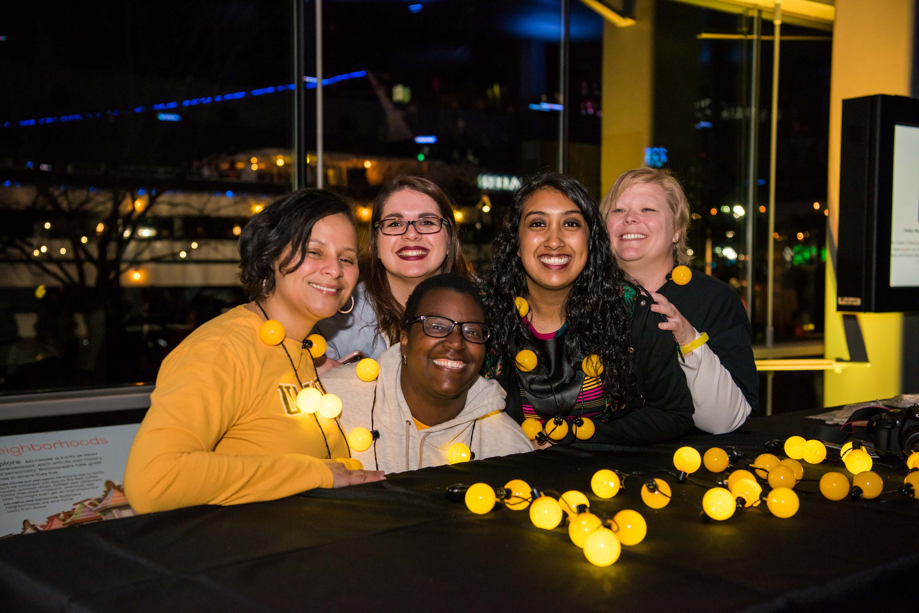 Group of 5 women pose behind table at alumni reception table