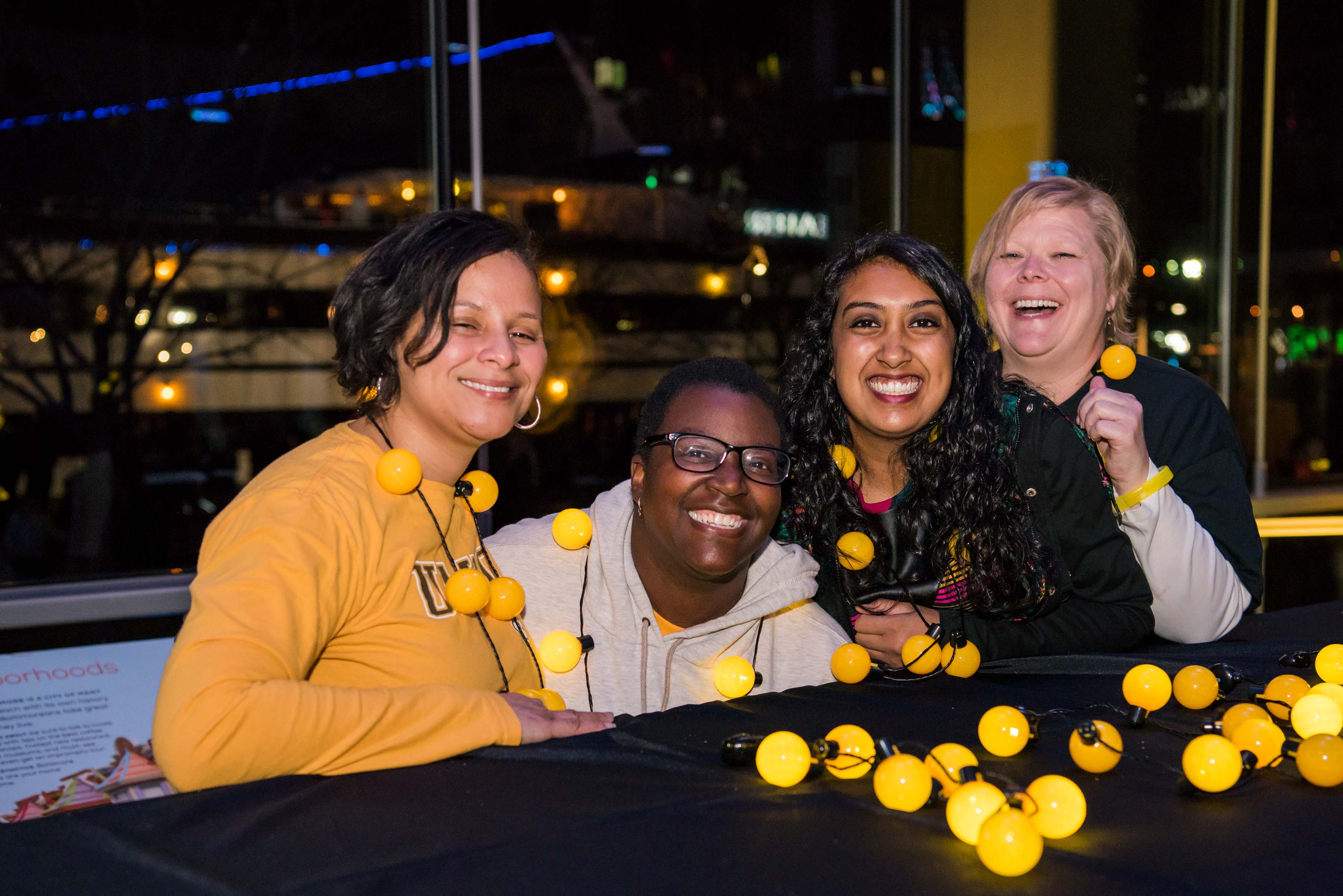 Group of four women pose together behind table at pier 5 reception