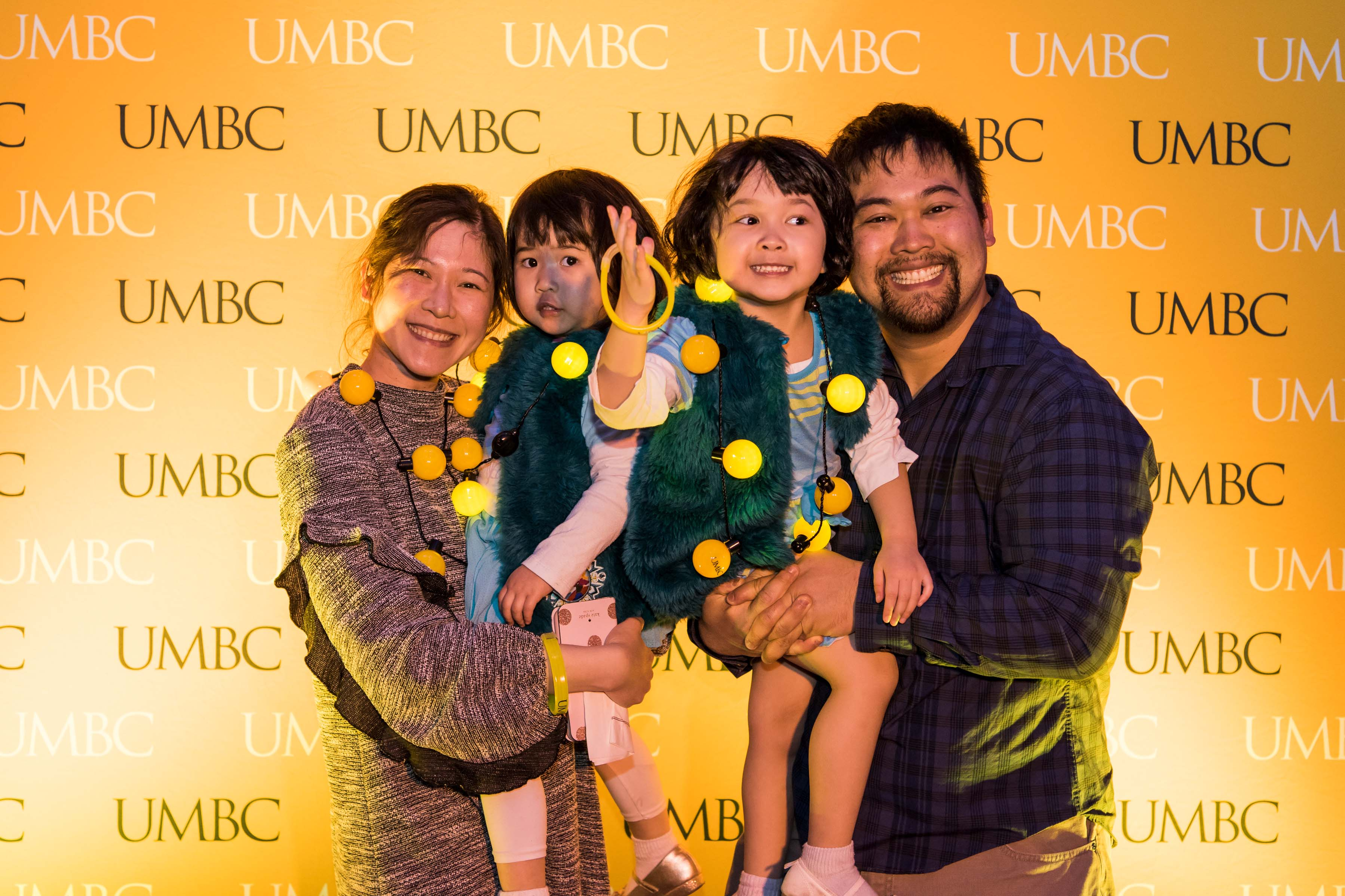 Family pose in front of UMBC wall at Pier 5 reception
