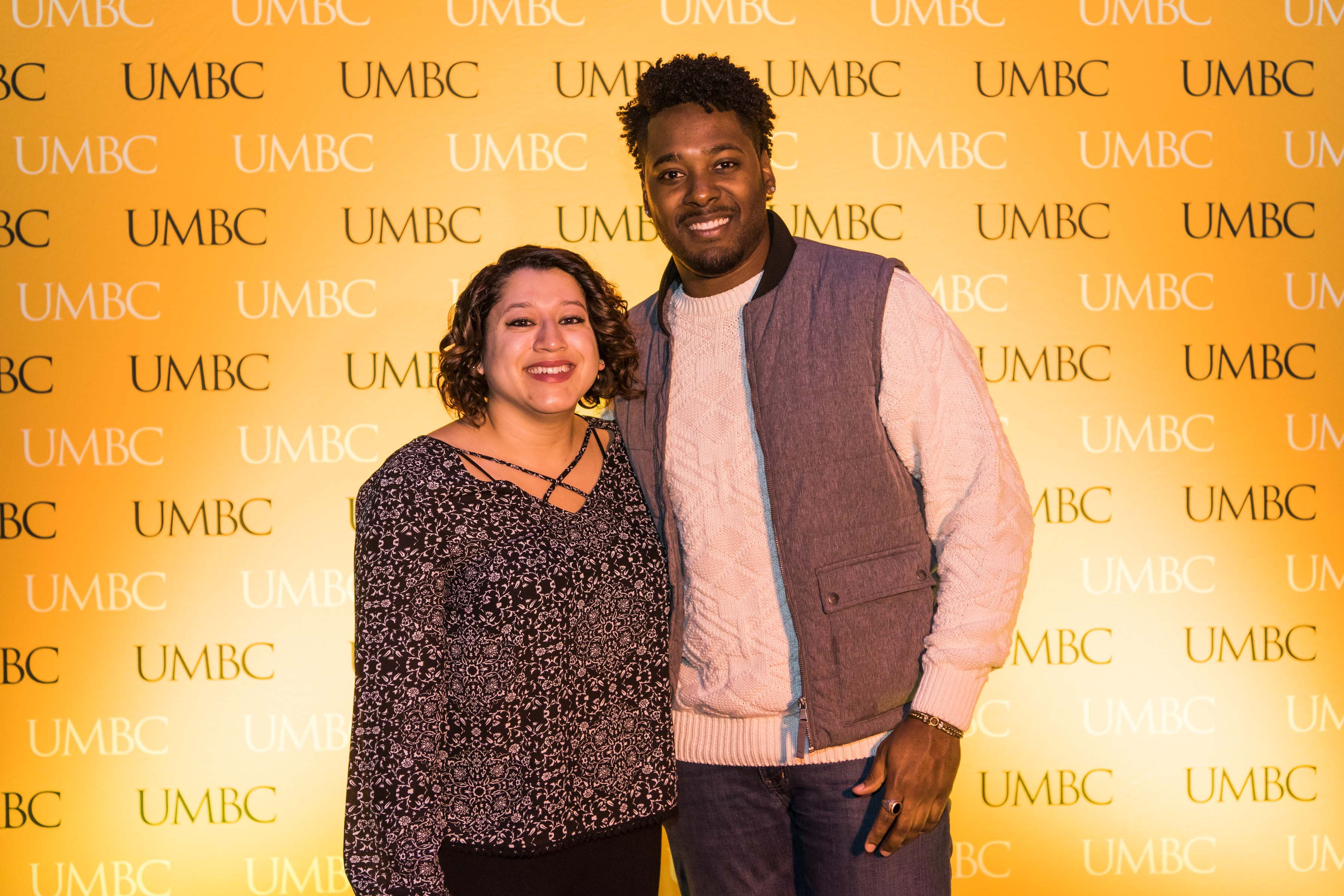 Man and woman pose in front of UMBC wall at Pier 5 reception