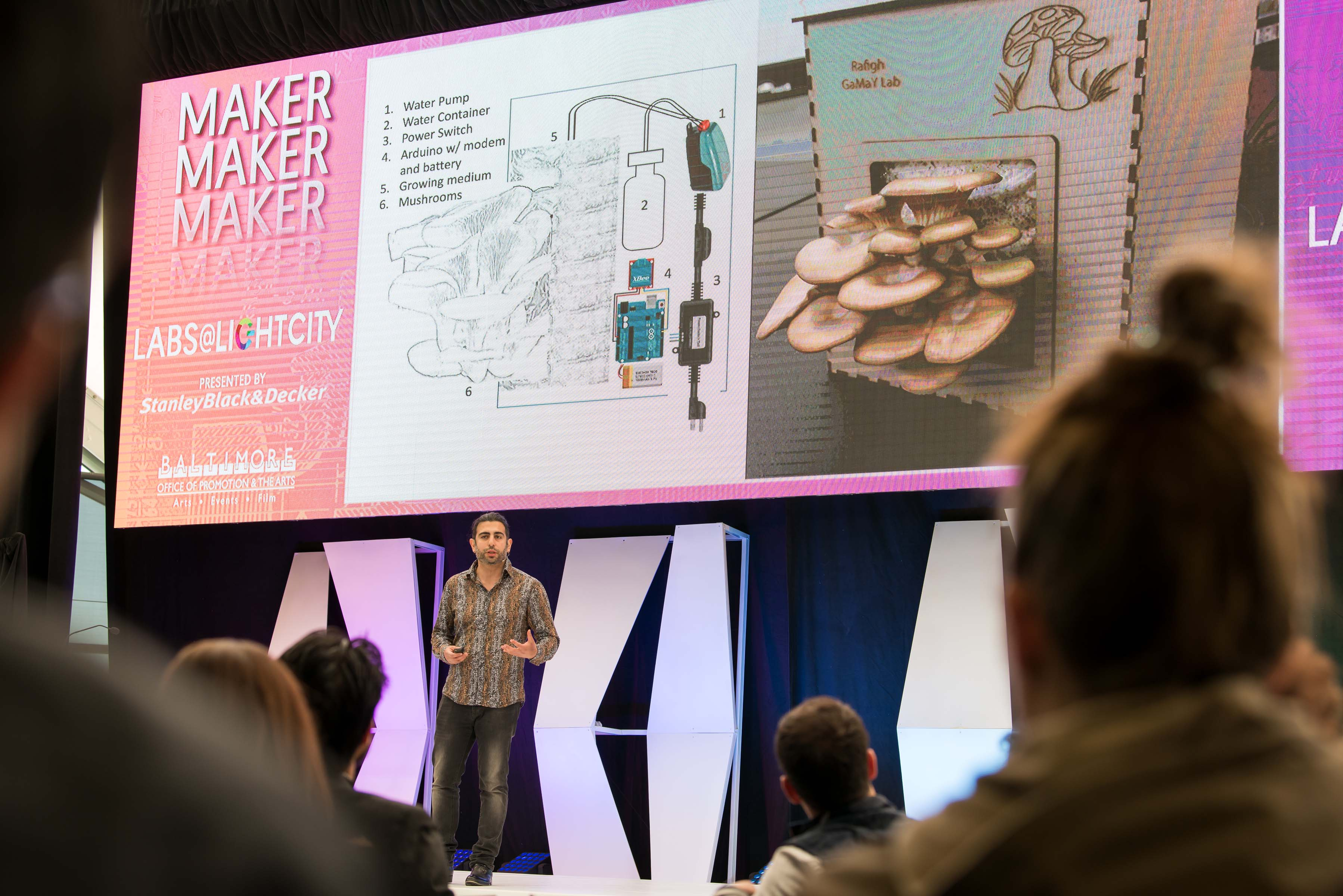Man stands on stage presenting his work with mushroom