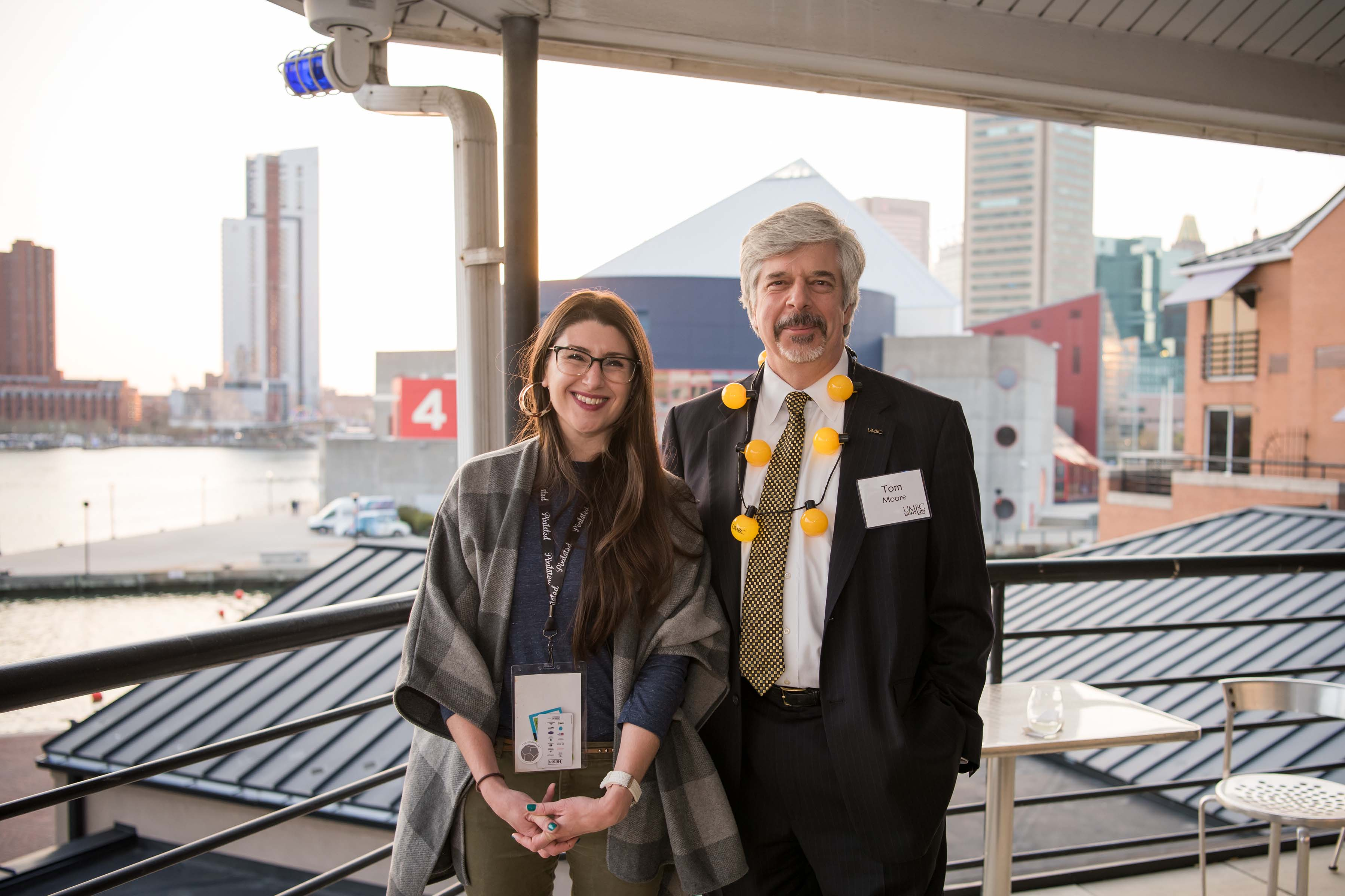 Tom Moore and woman pose outside at Pier5 reception