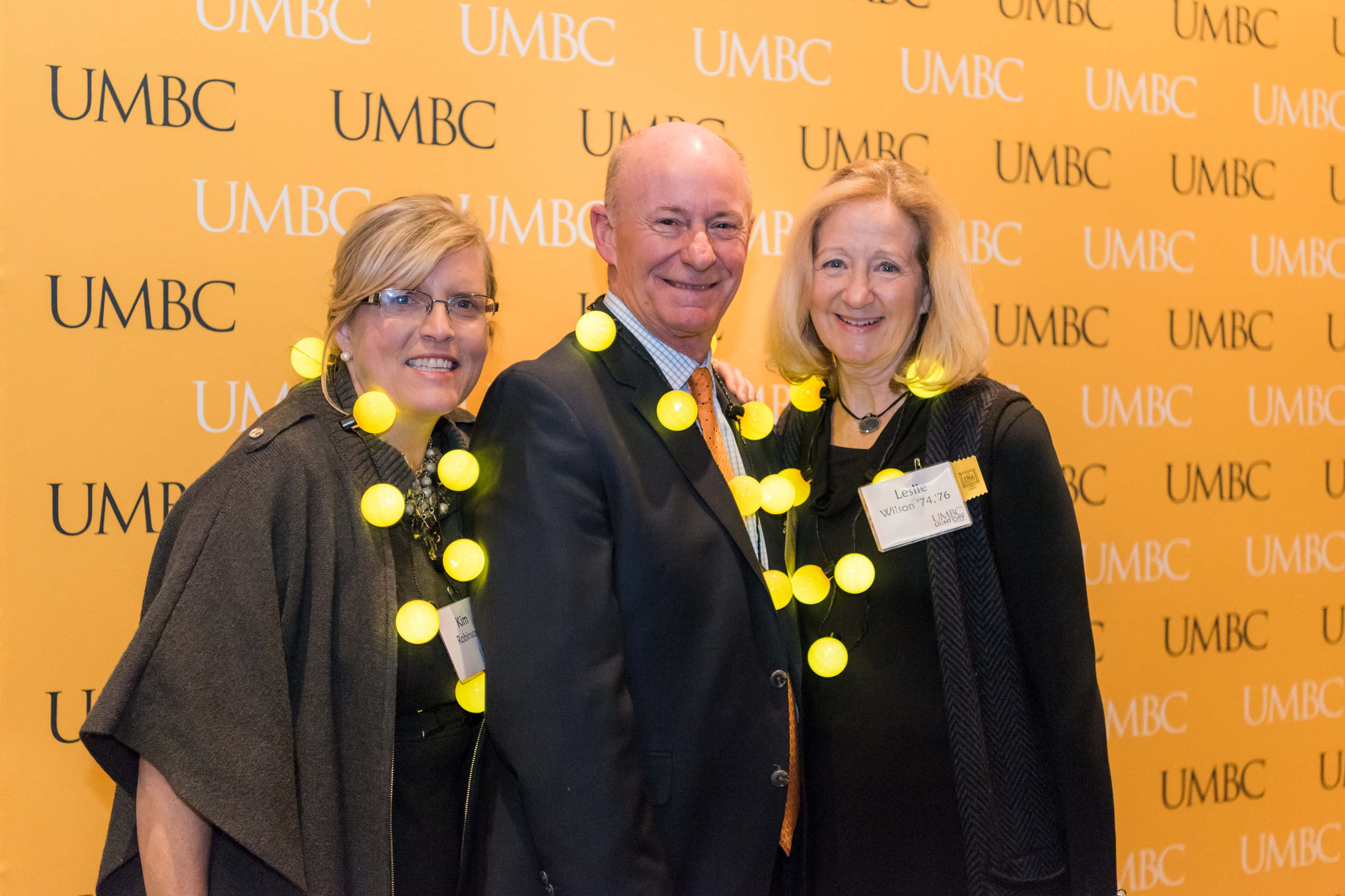 Group of three crowd together in front of UMBC wall