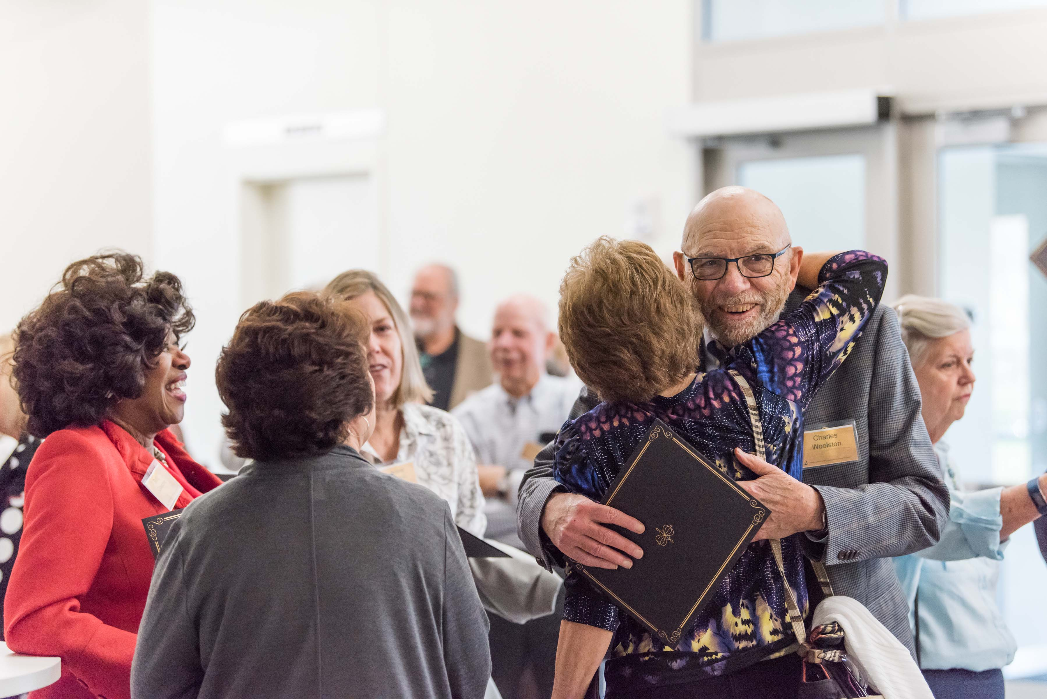 People hug at Wisdom Institute lunch