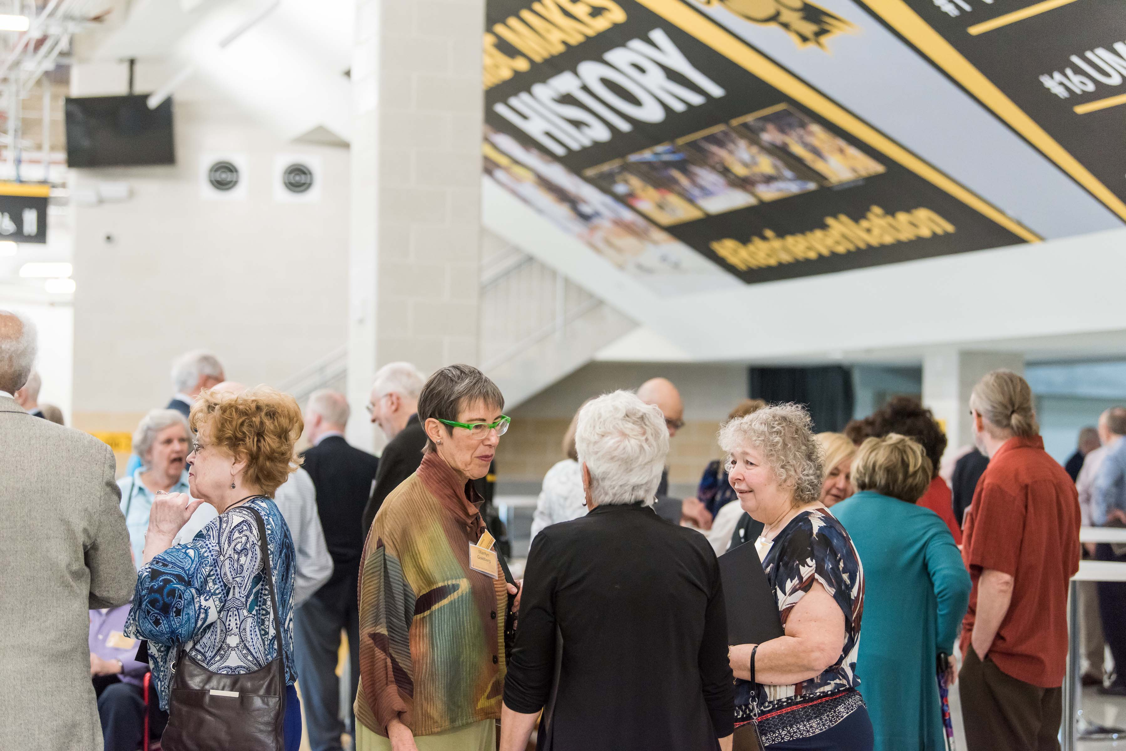 People talking UMBC Makes History sign in background at Wisdom Institute lunch