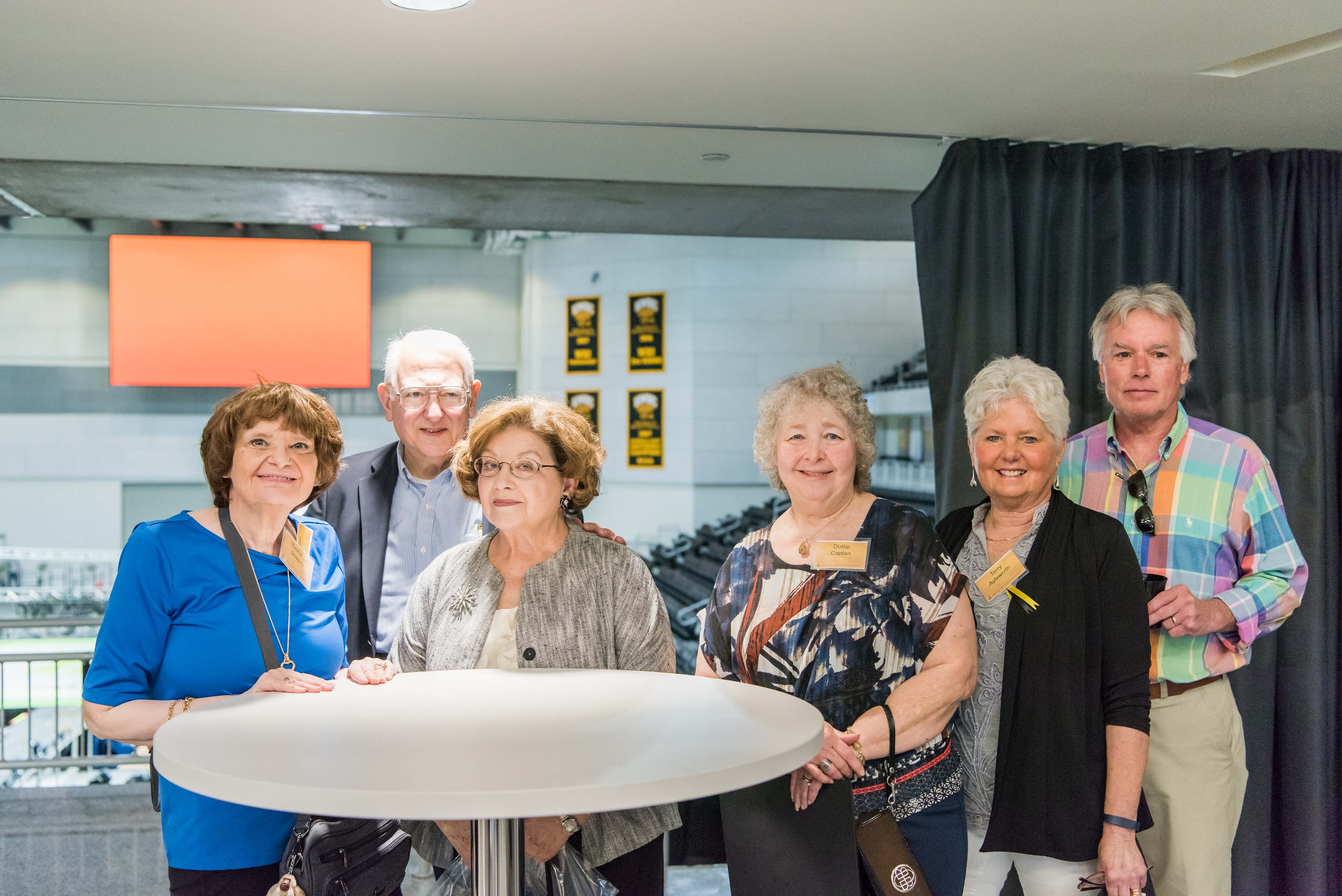 Group of six pose around table at Wisdom Institute lunch