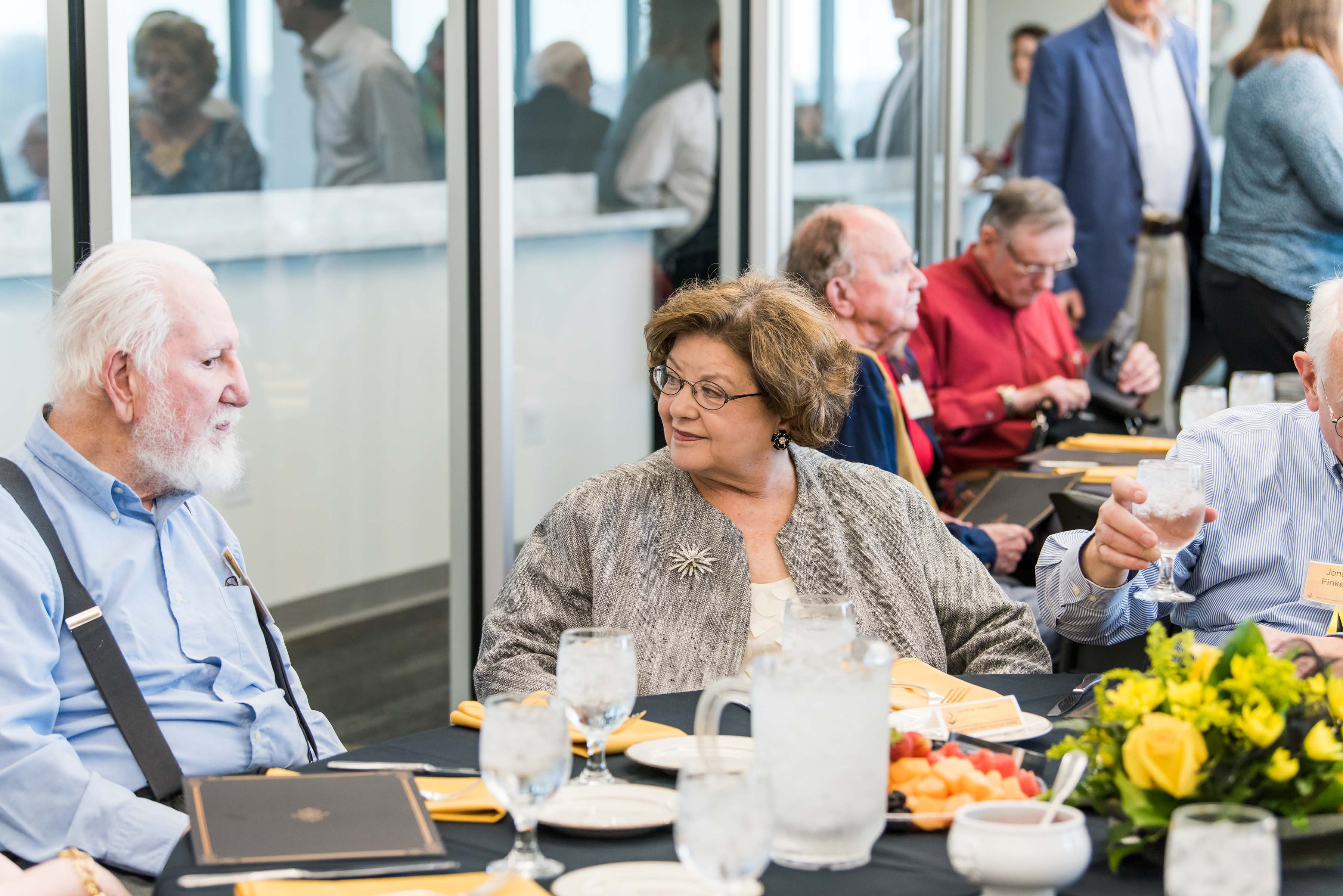 People sit at table with spread at Wisdom Institute lunch