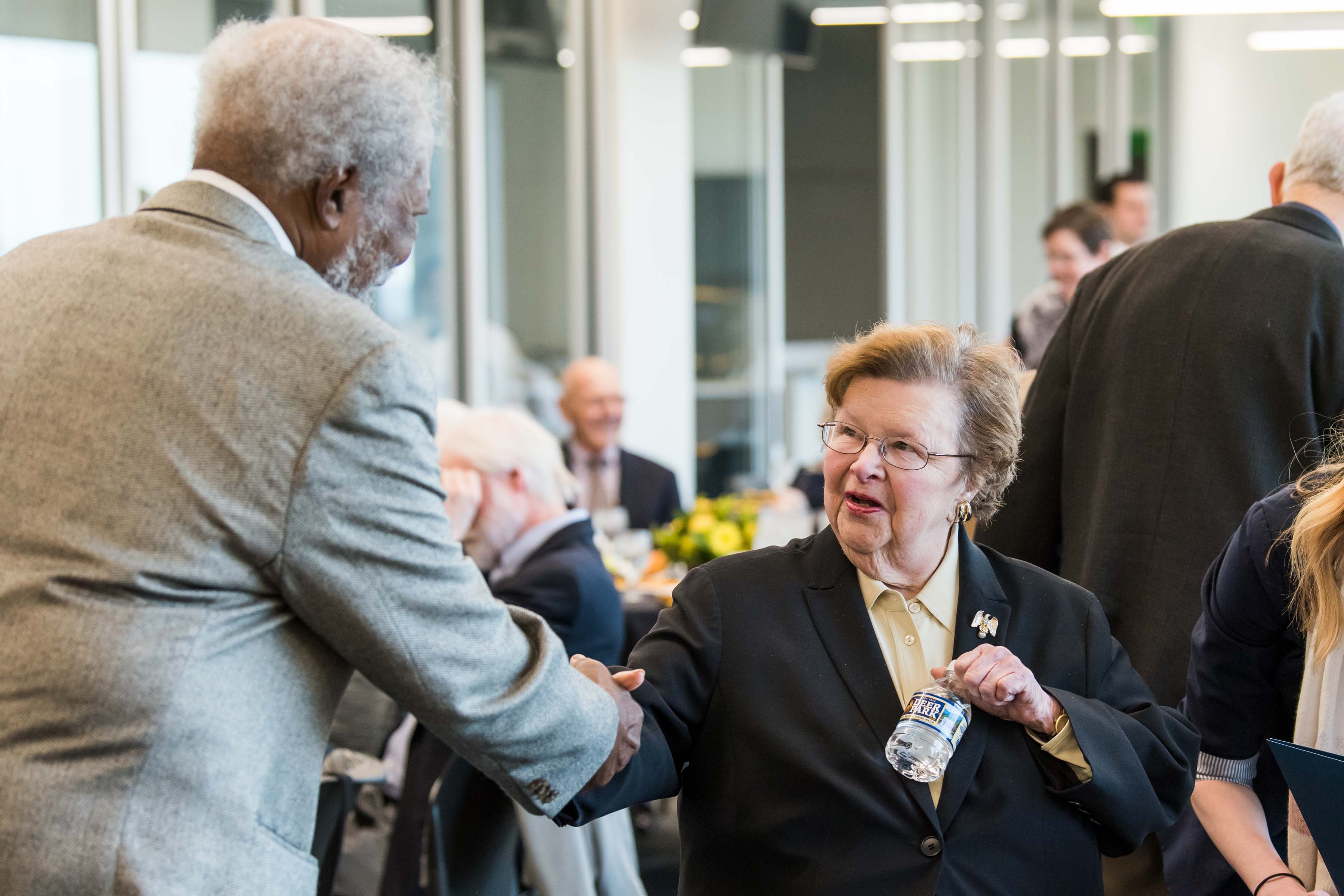 Two people shake hands at Wisdom Institute lunch