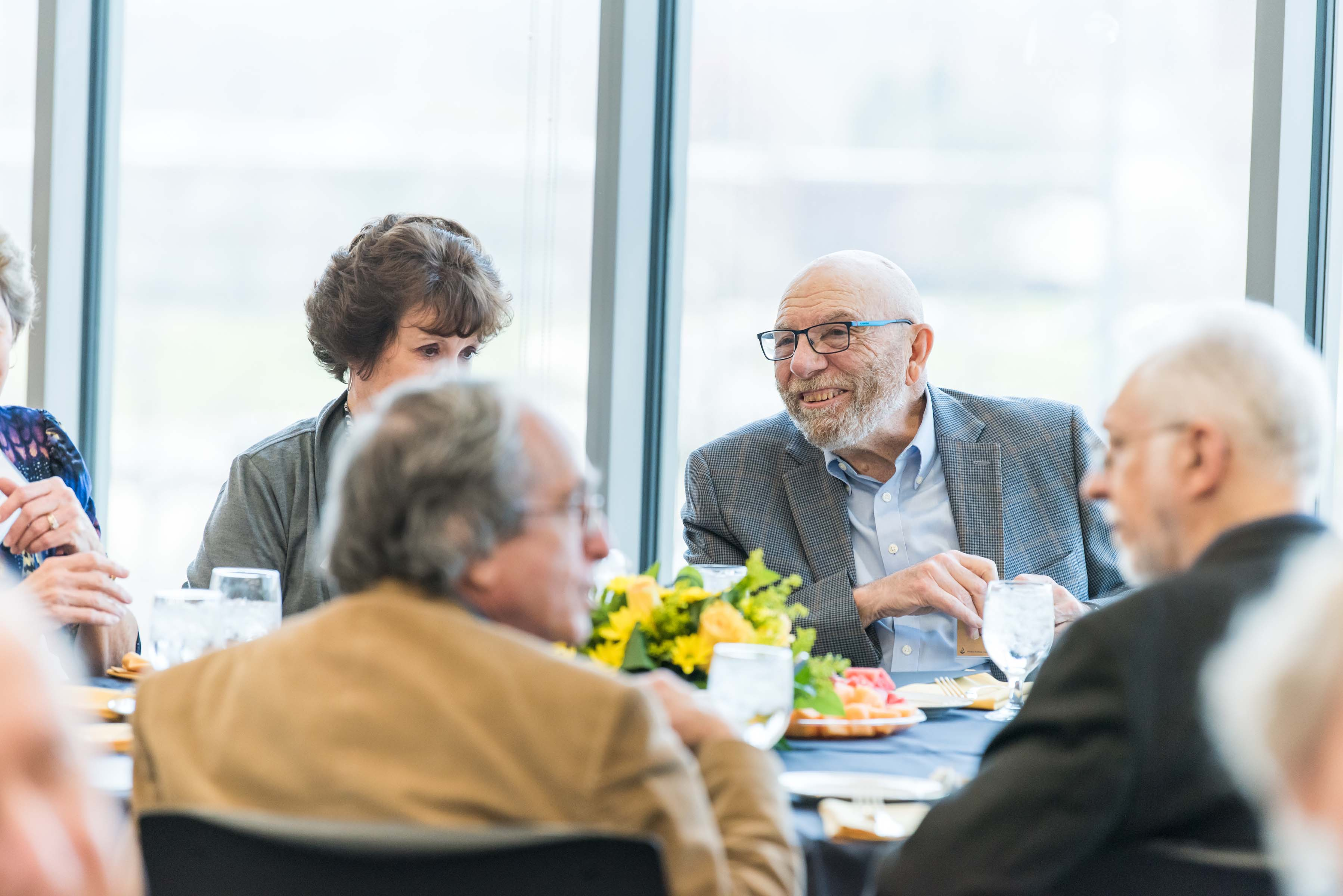 Man smiles at table at Wisdom Institute lunch