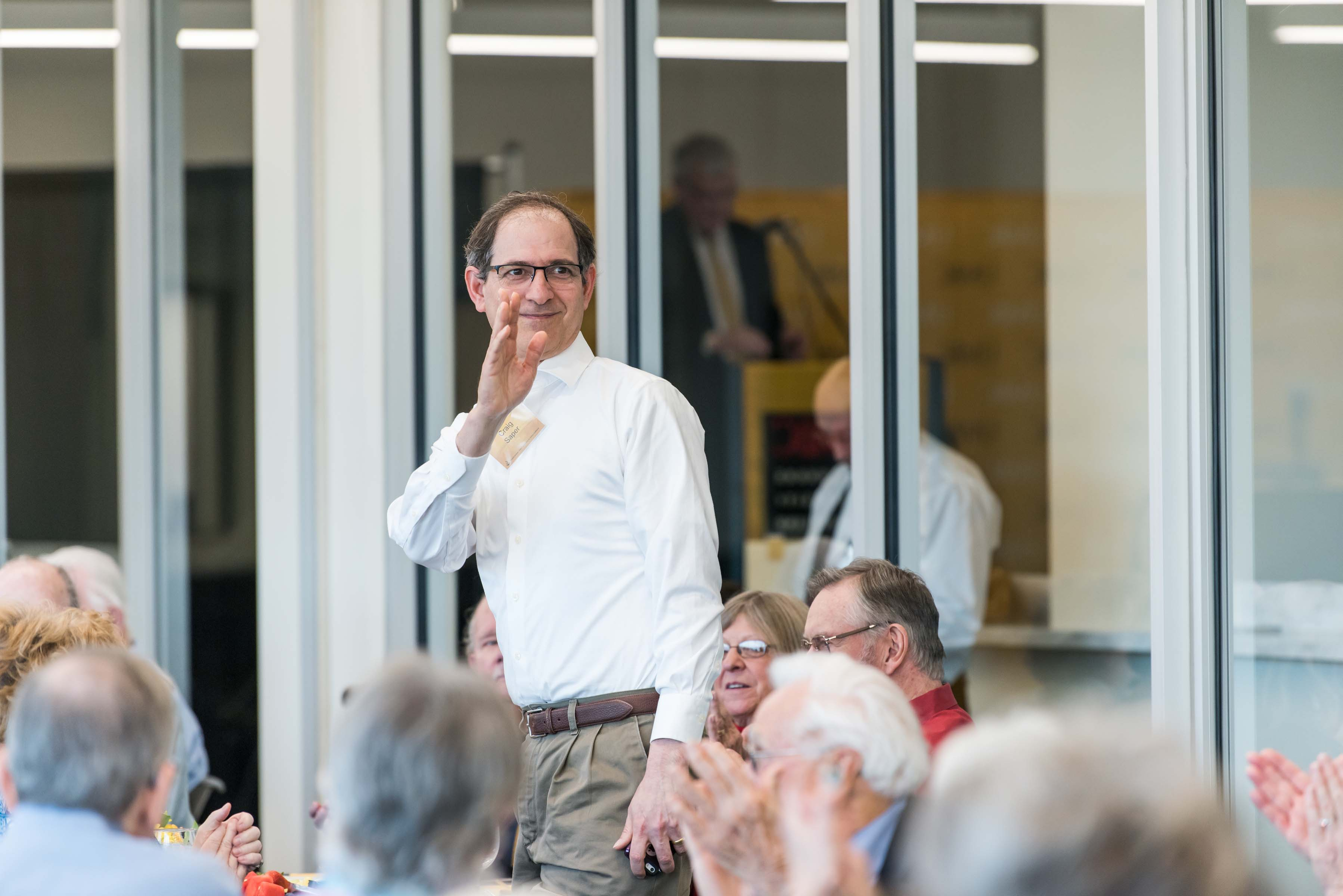 man stands up to wave at Wisdom Institute lunch