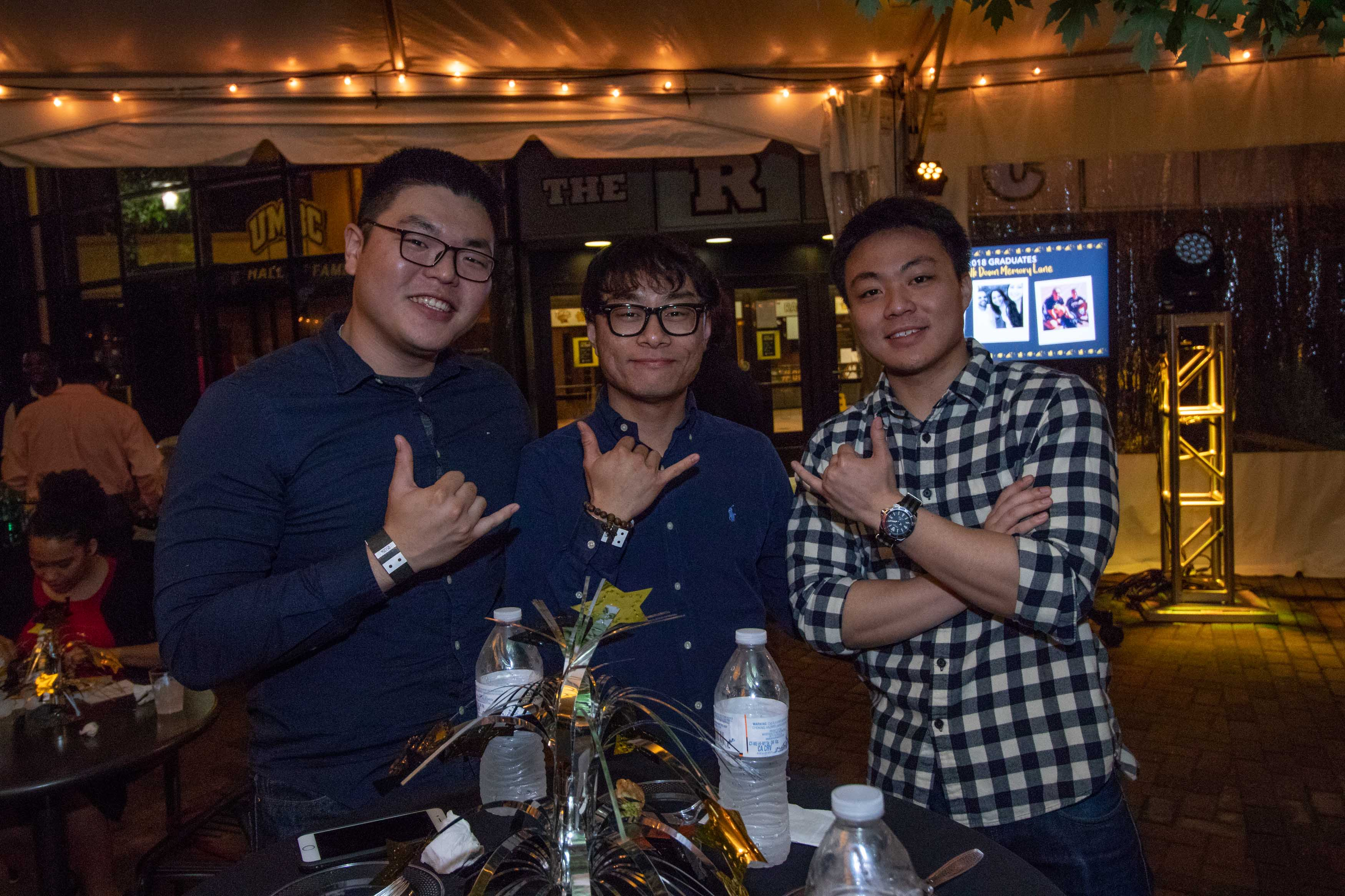 Three men hold out shaka hand