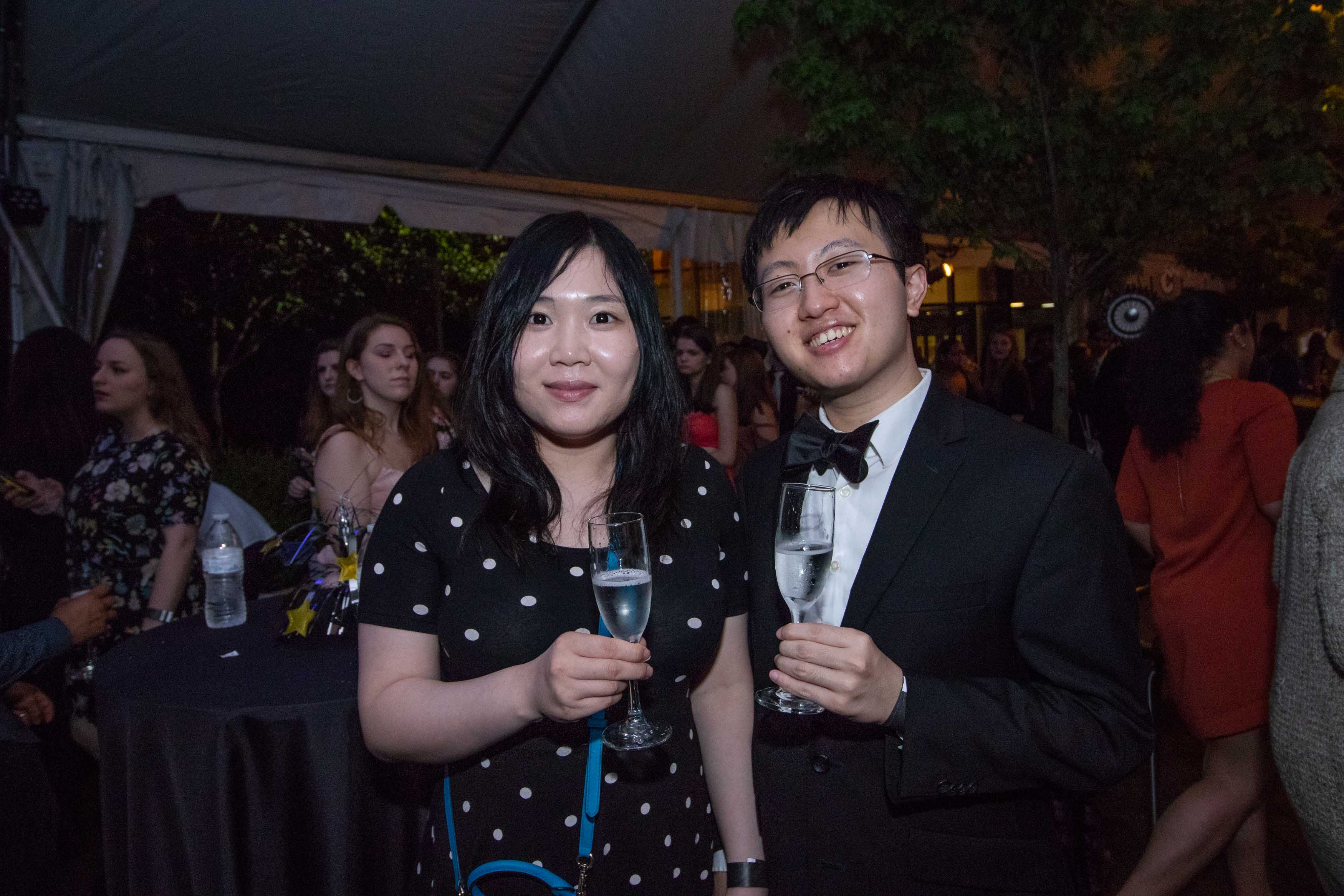 Man in bowtie poses with woman and wine glass