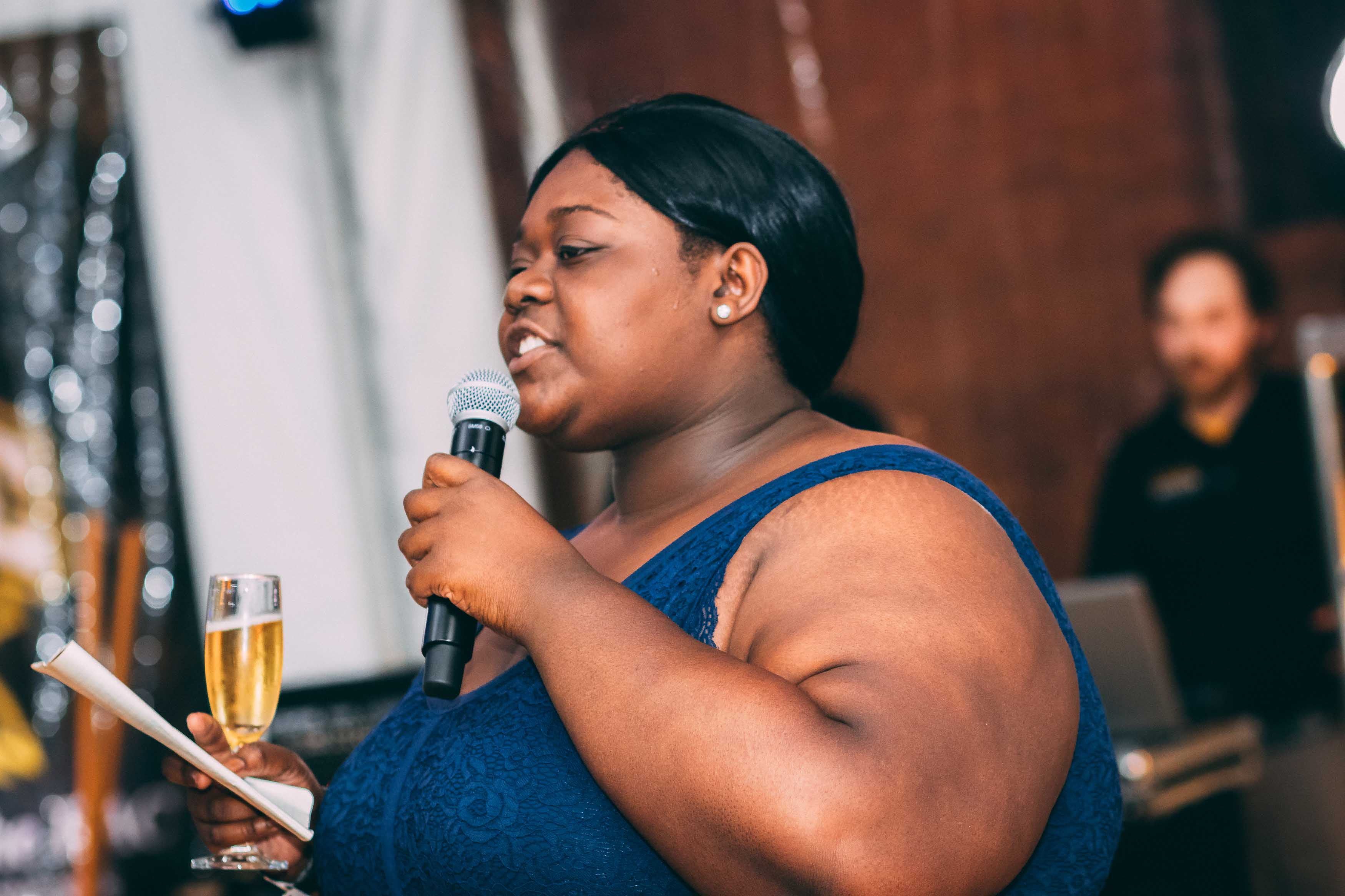 Woman gives speech mic in one hand and paper and wine in the other