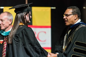 Hrabowski shakes hand and speaks to student at graduation