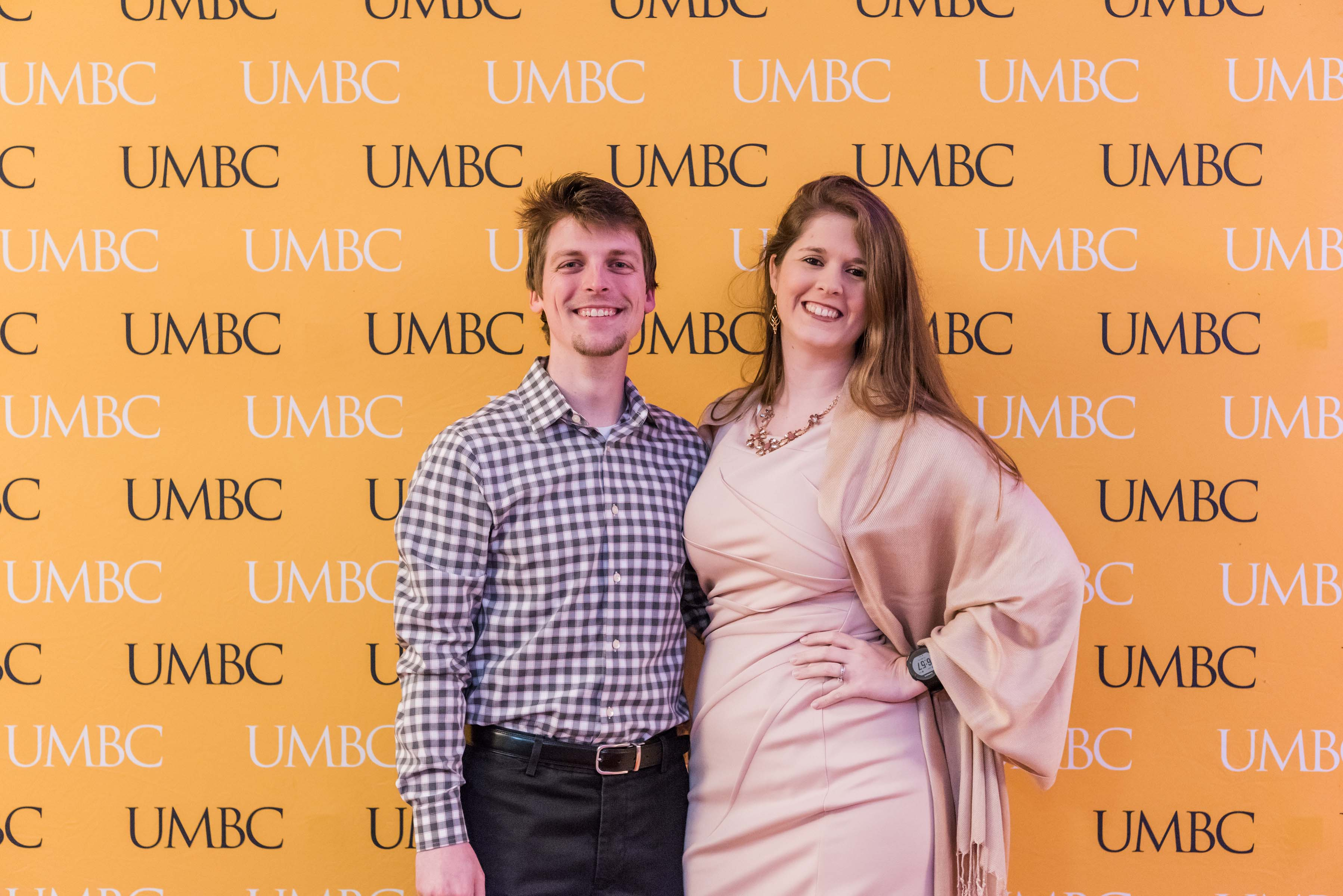 Man and women pose together in front of UMBC wall for wine tasting